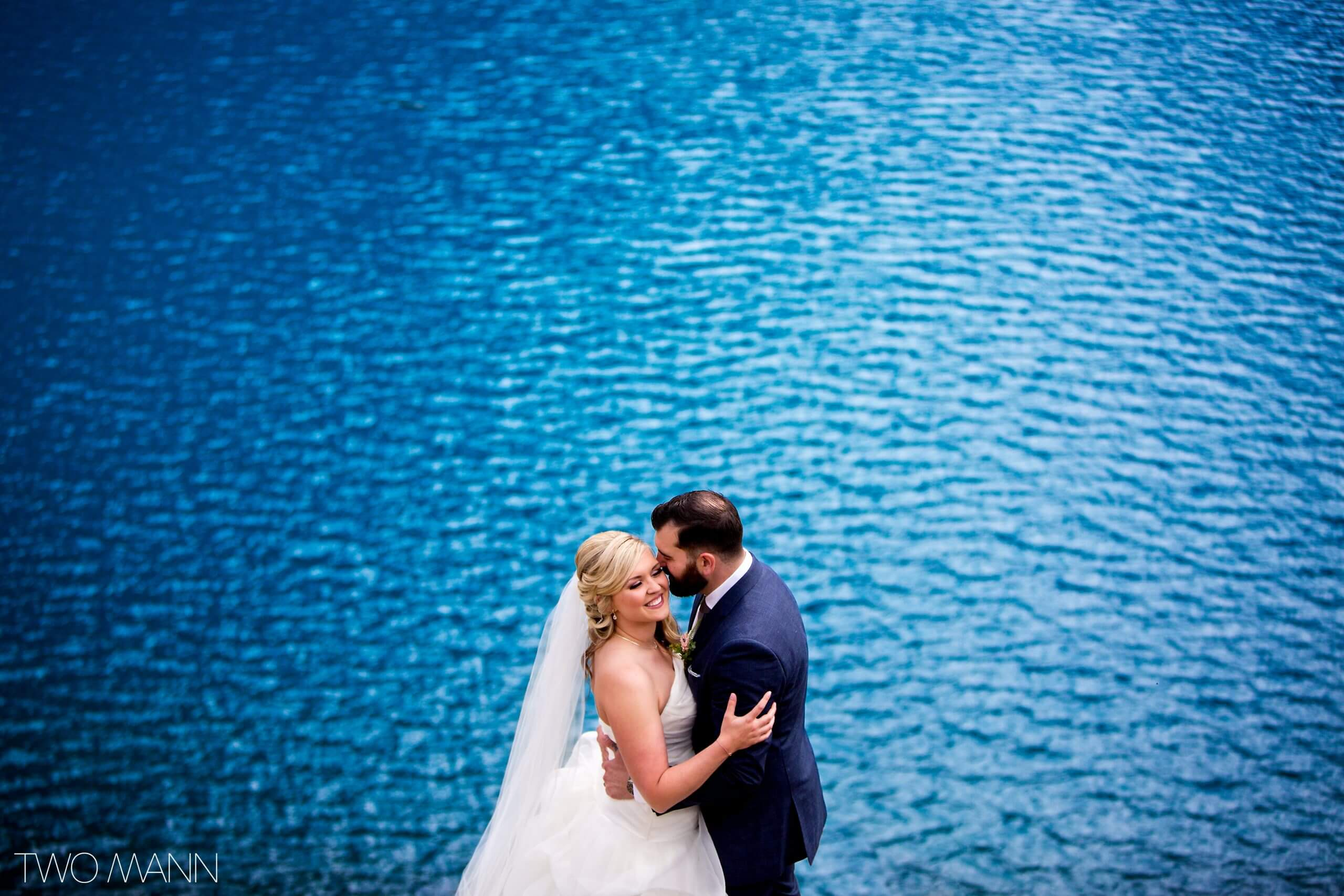 bride and groom embracing on the shores of Moraine Lake