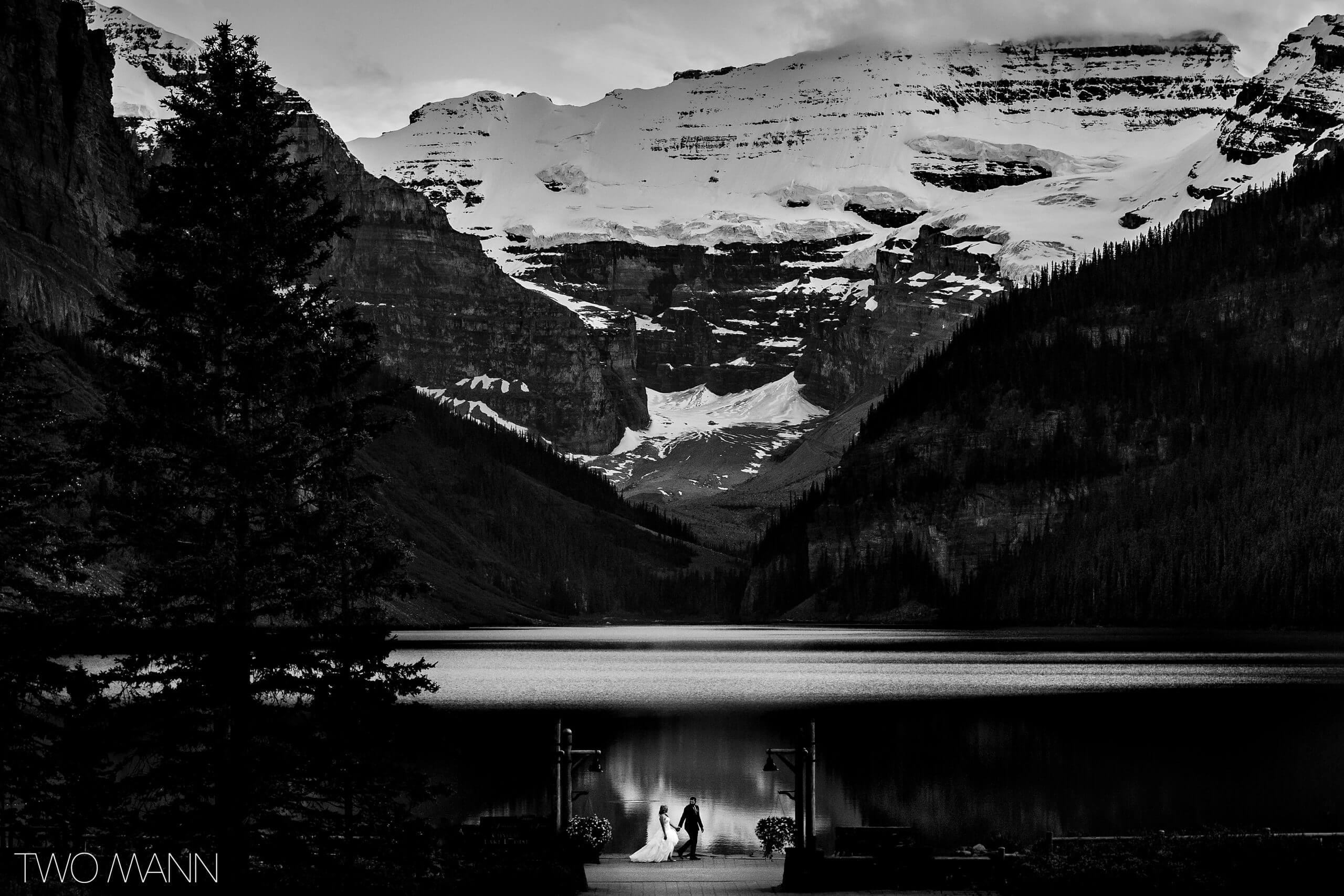bride and groom walking hand in hand on the shores of Lake Louise