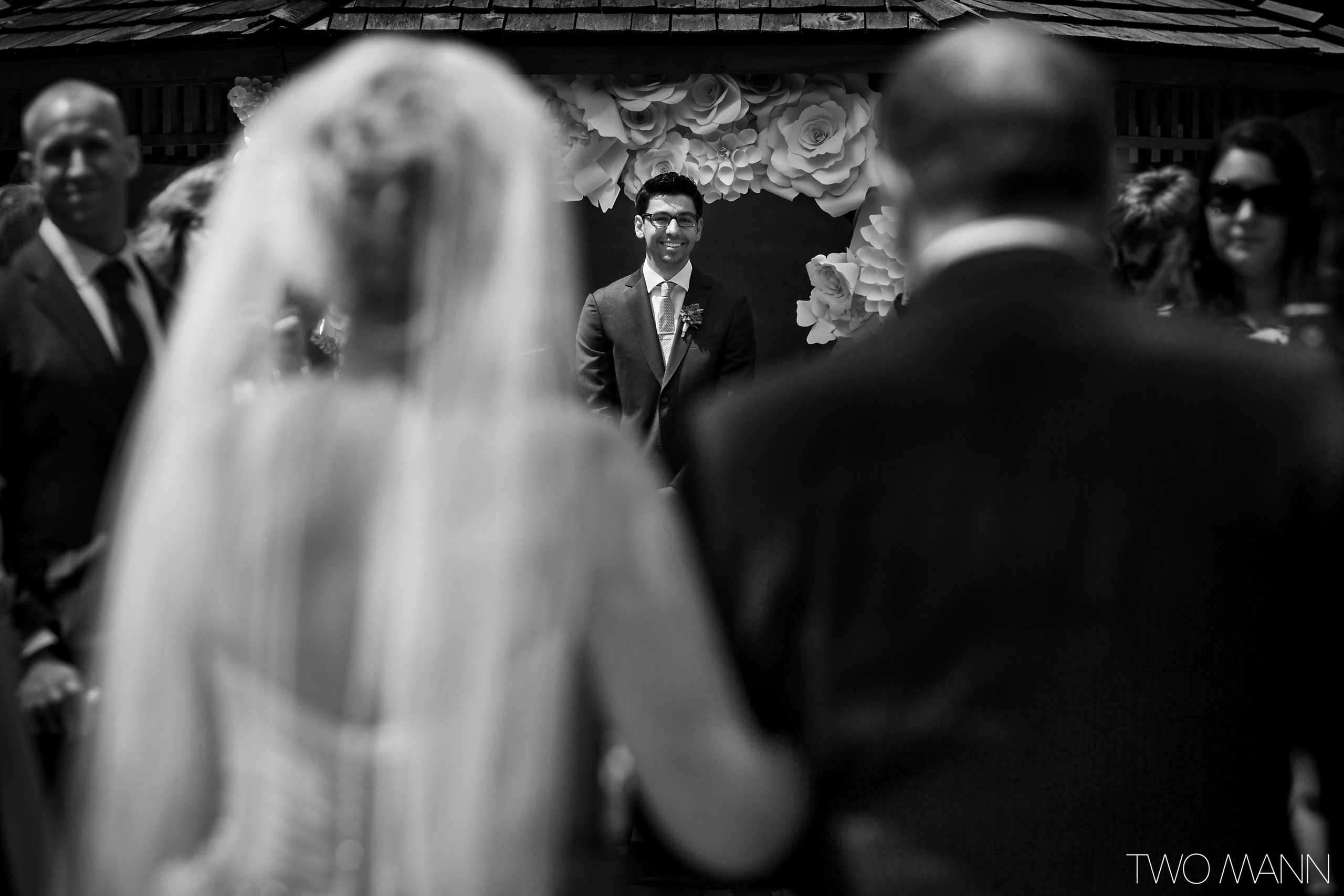 a groom waiting for his bride escorted by her father