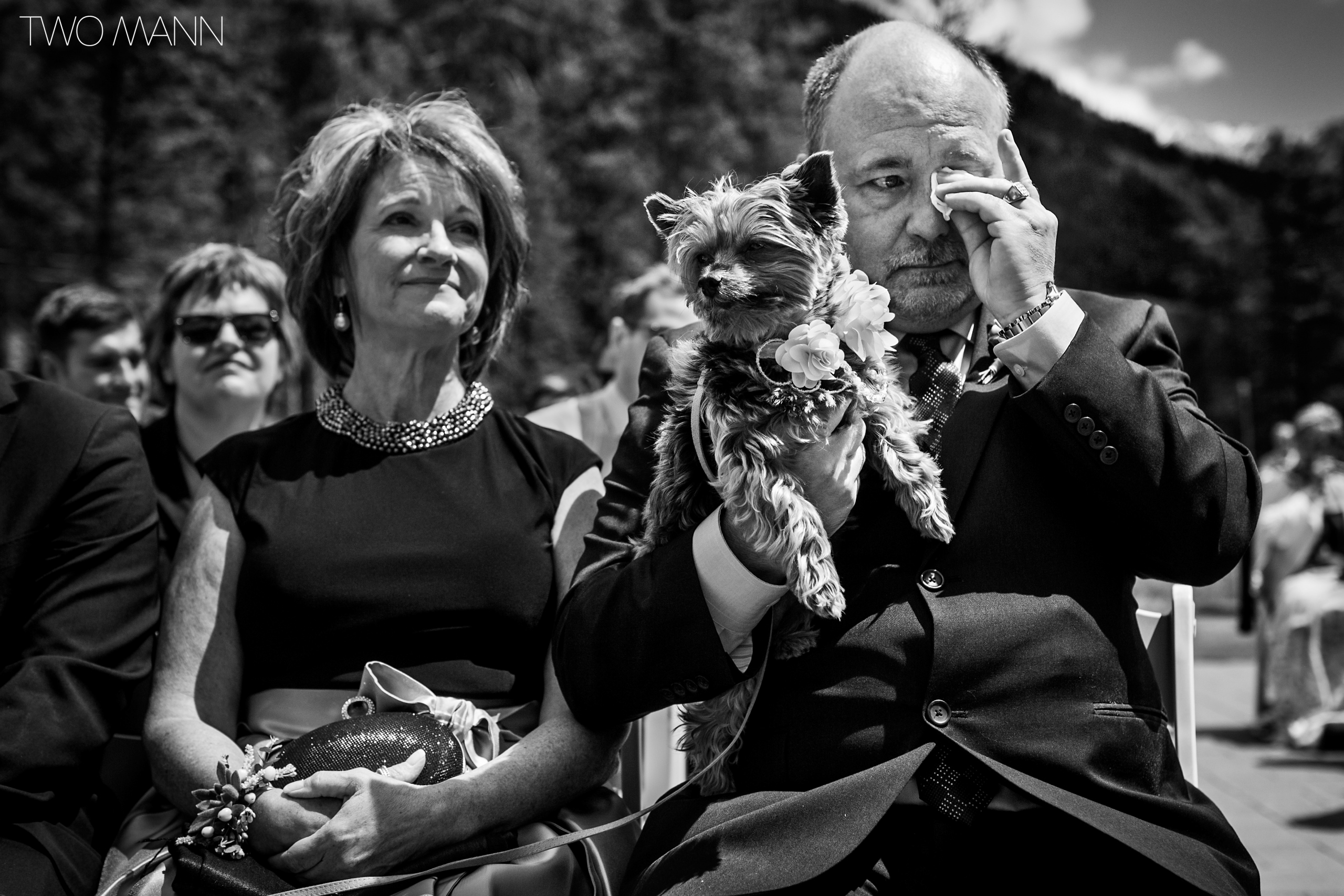 bride's emotional parents and their pet dog at wedding ceremony
