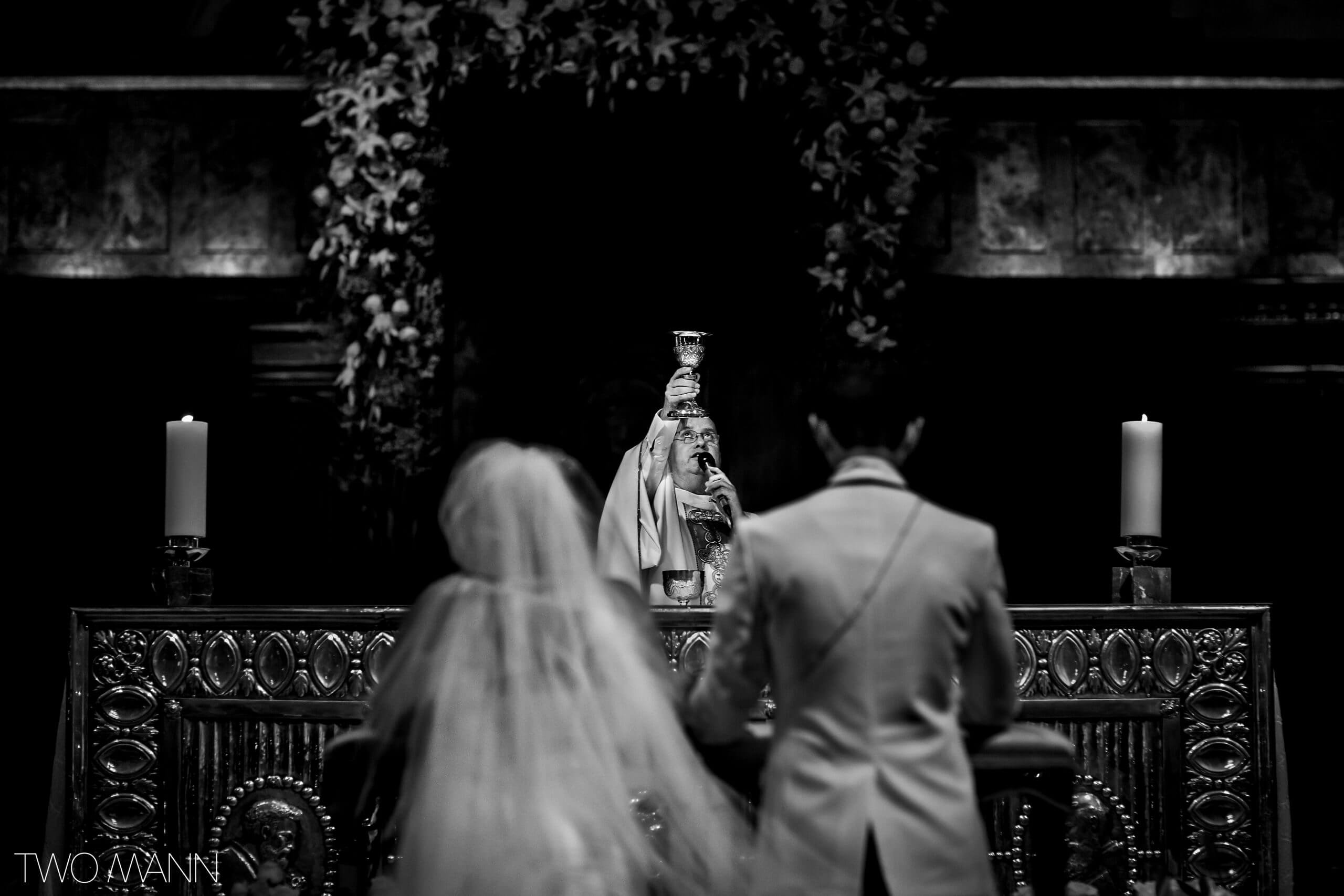 bride and groom pray at wedding ceremony in a church