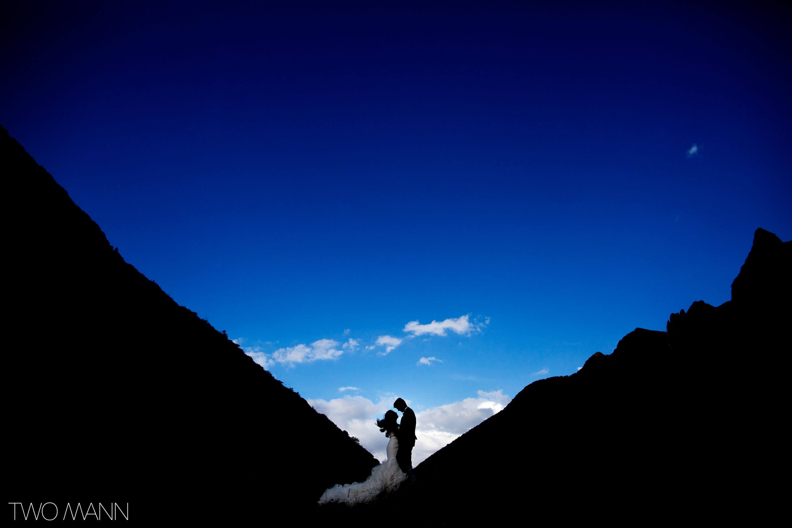 bride and groom embracing in mountains