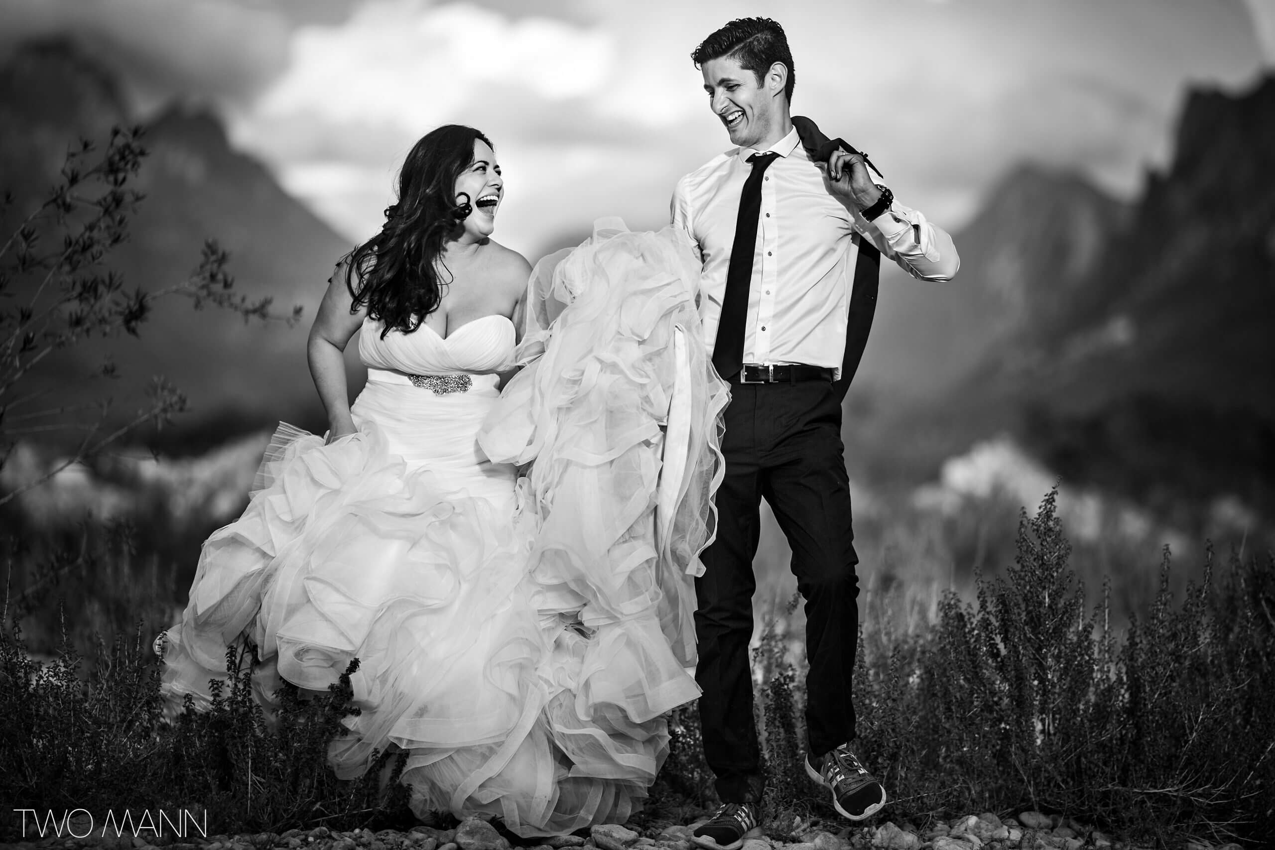 mexican bride and groom laughing on top of a mountain