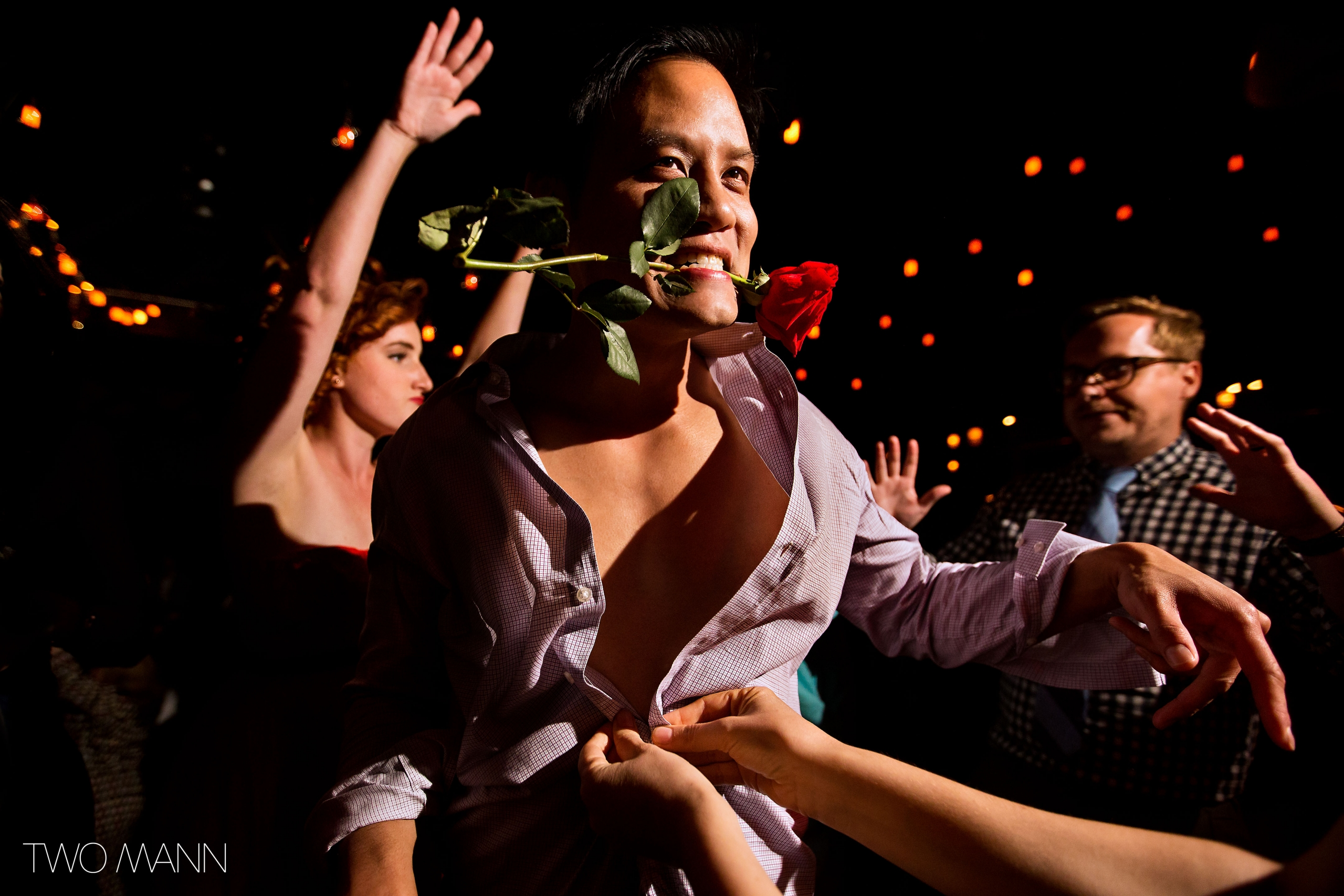 a young man on the dance floor with a red rose in mouth