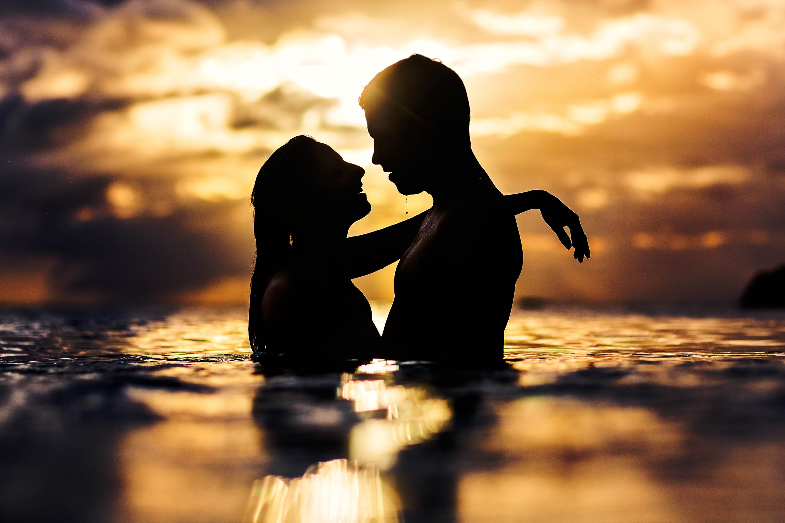 Silhouette of couple embracing in ocean at sunset