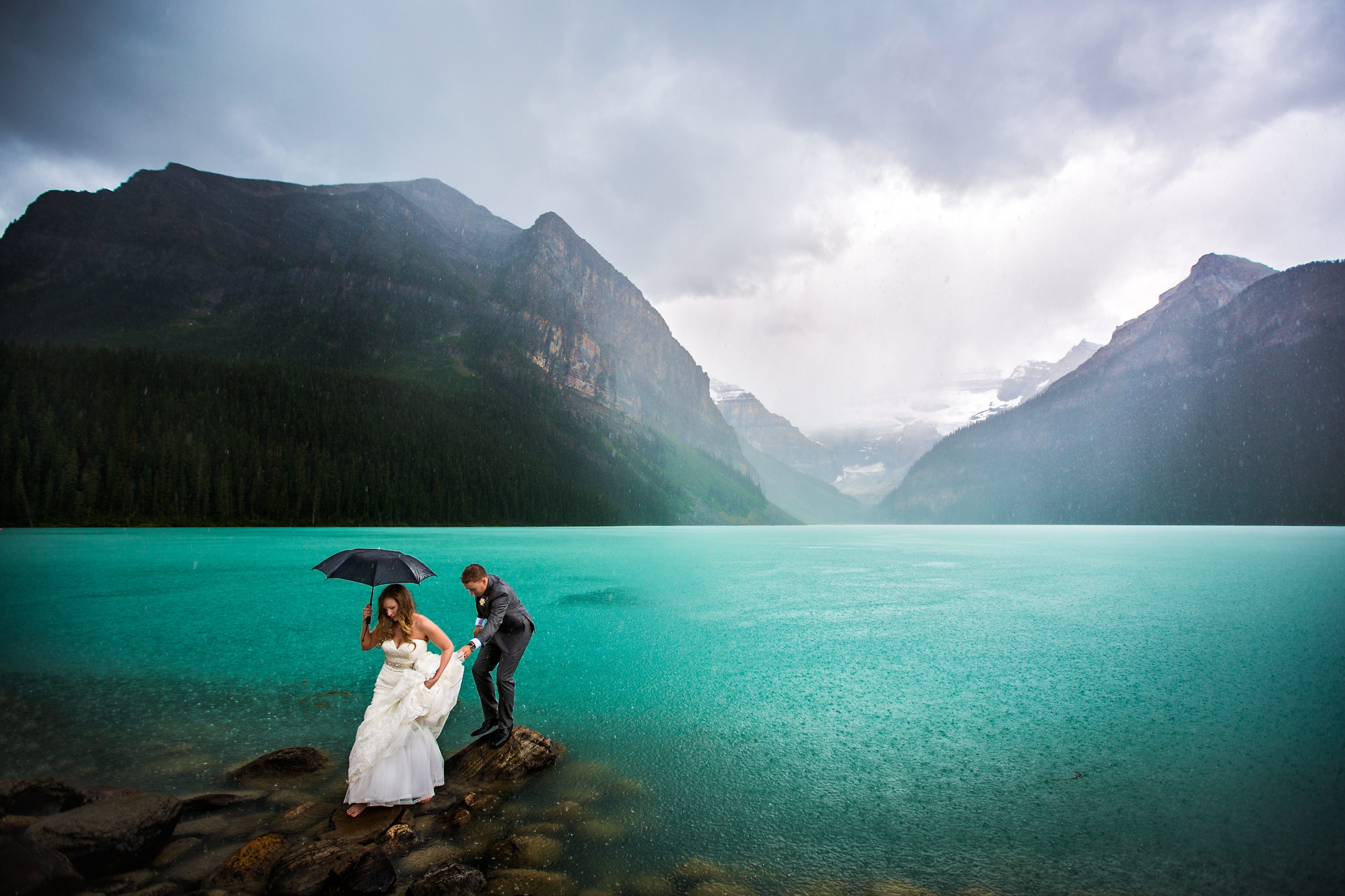 Bride and groom walking across rocks in lake in Canadian Rockies