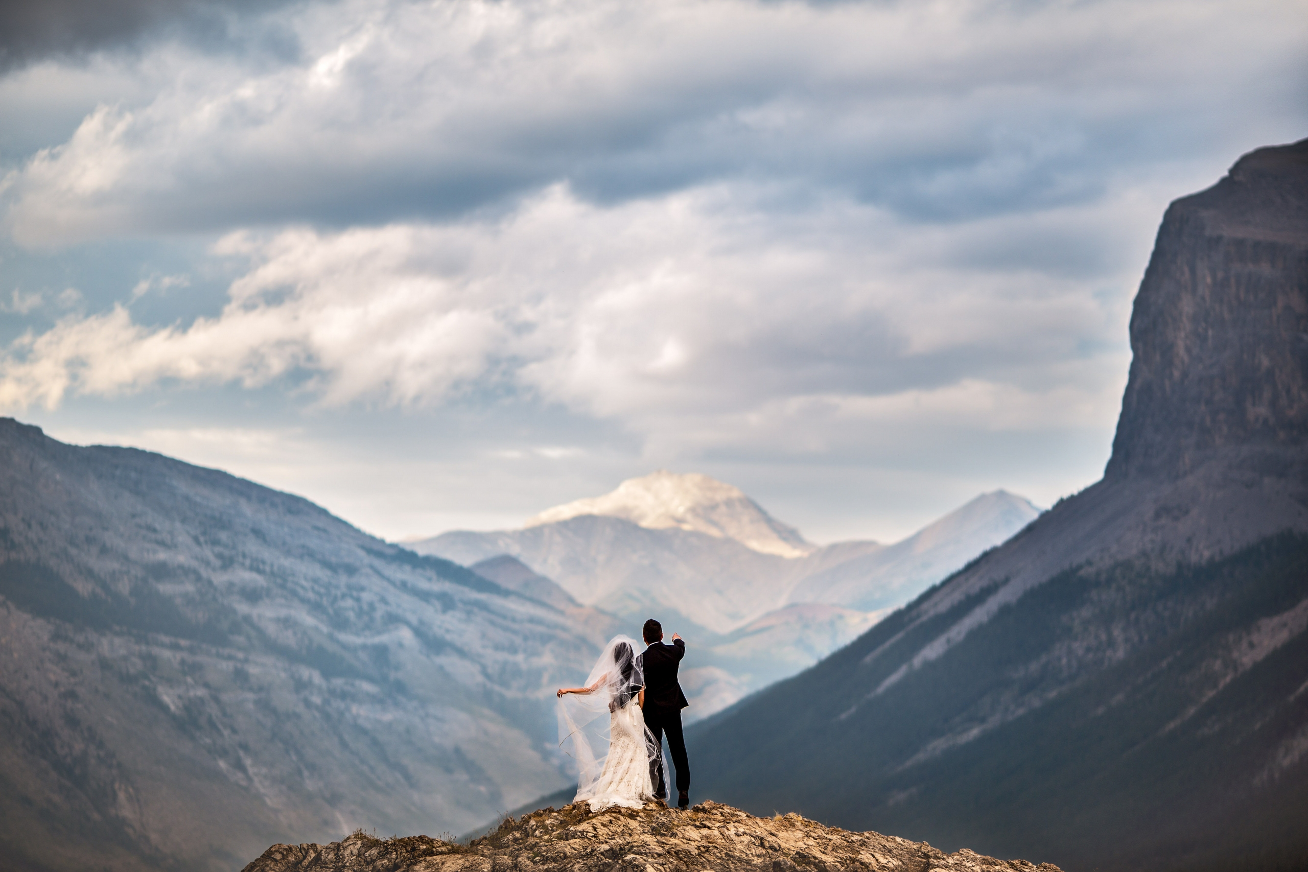 Bride in wedding dress and groom pointing ahead at mountains in the distance