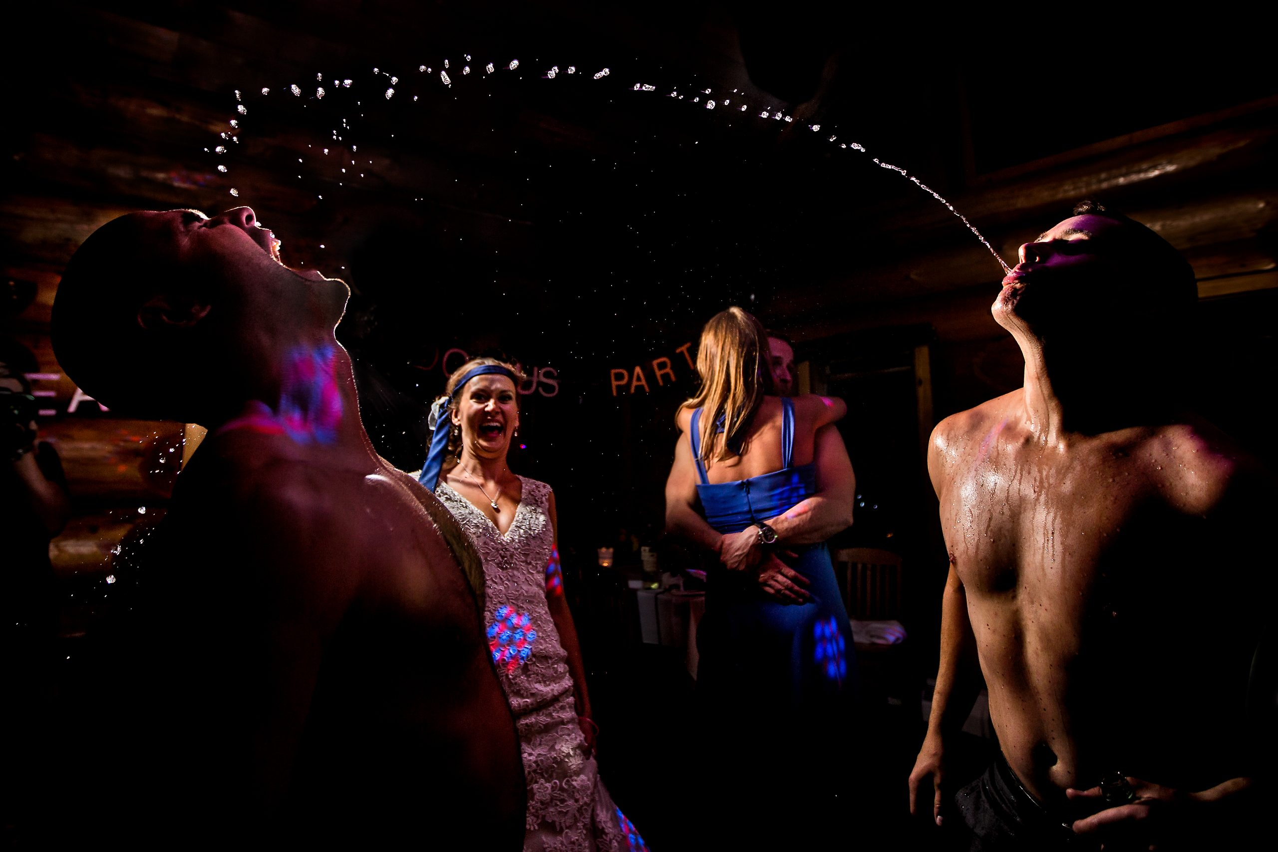 Shirtless groom spitting wine across dance floor into groomsman's open mouth with bride cheering on at Island Lake Lodge in Fernie, BC