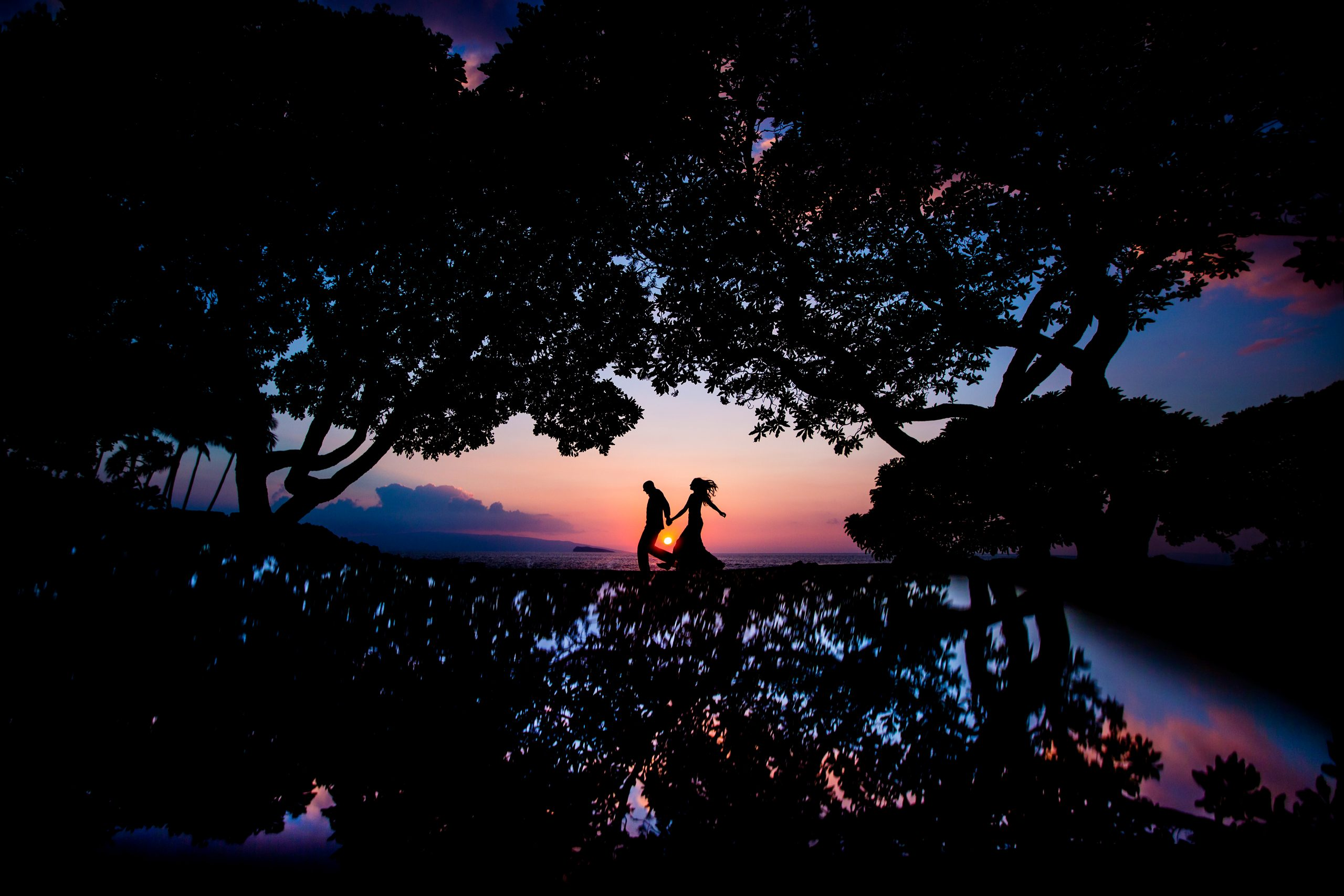 Silhouette of bride and groom running at sunset in Maui, Hawaii