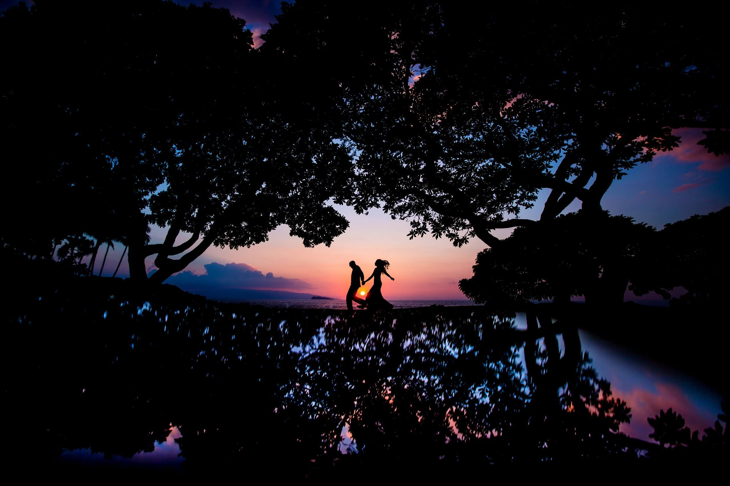 Couple holding hands walking by the beach at dusk