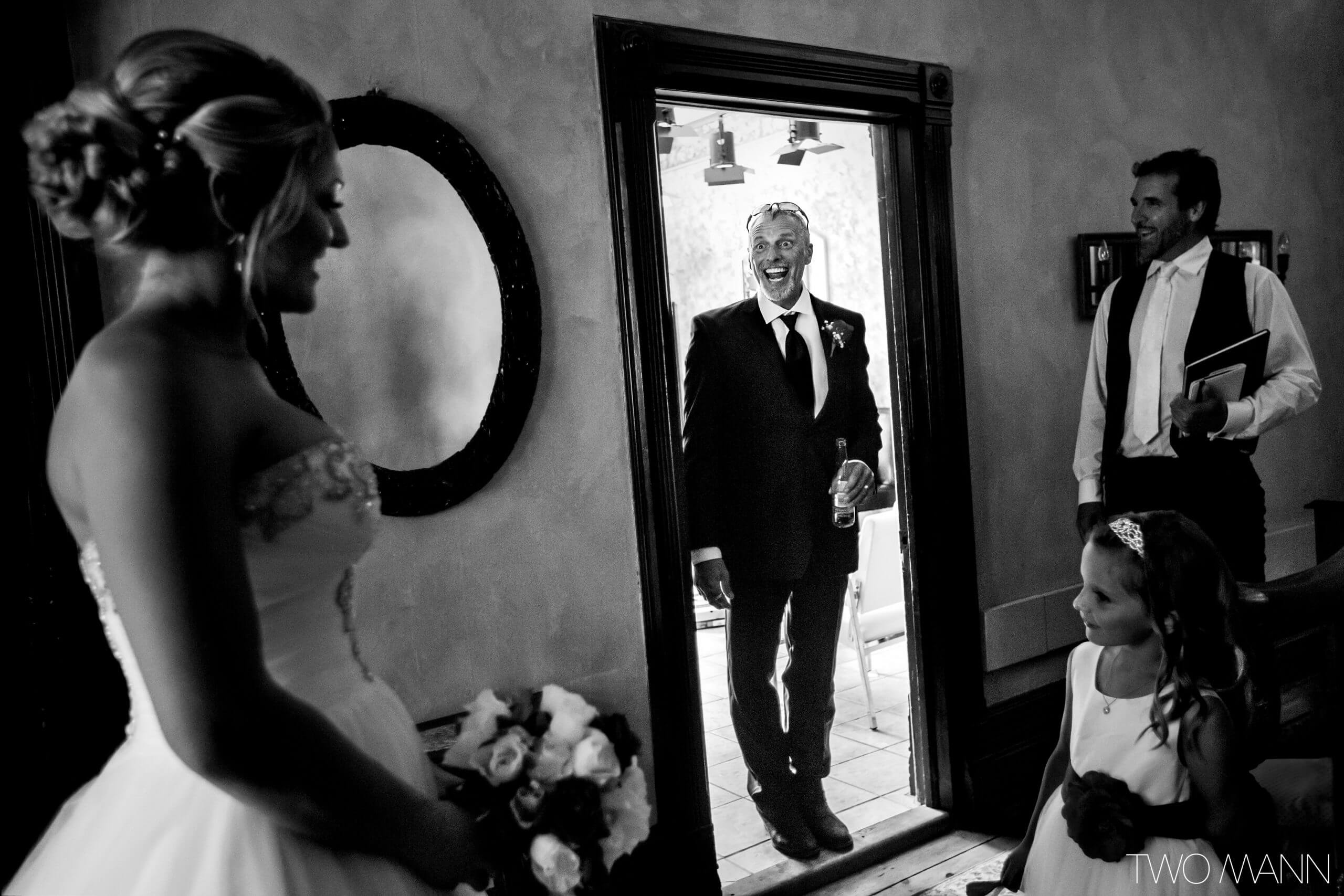 the father of a bride first seeing her daughter in her wedding dress