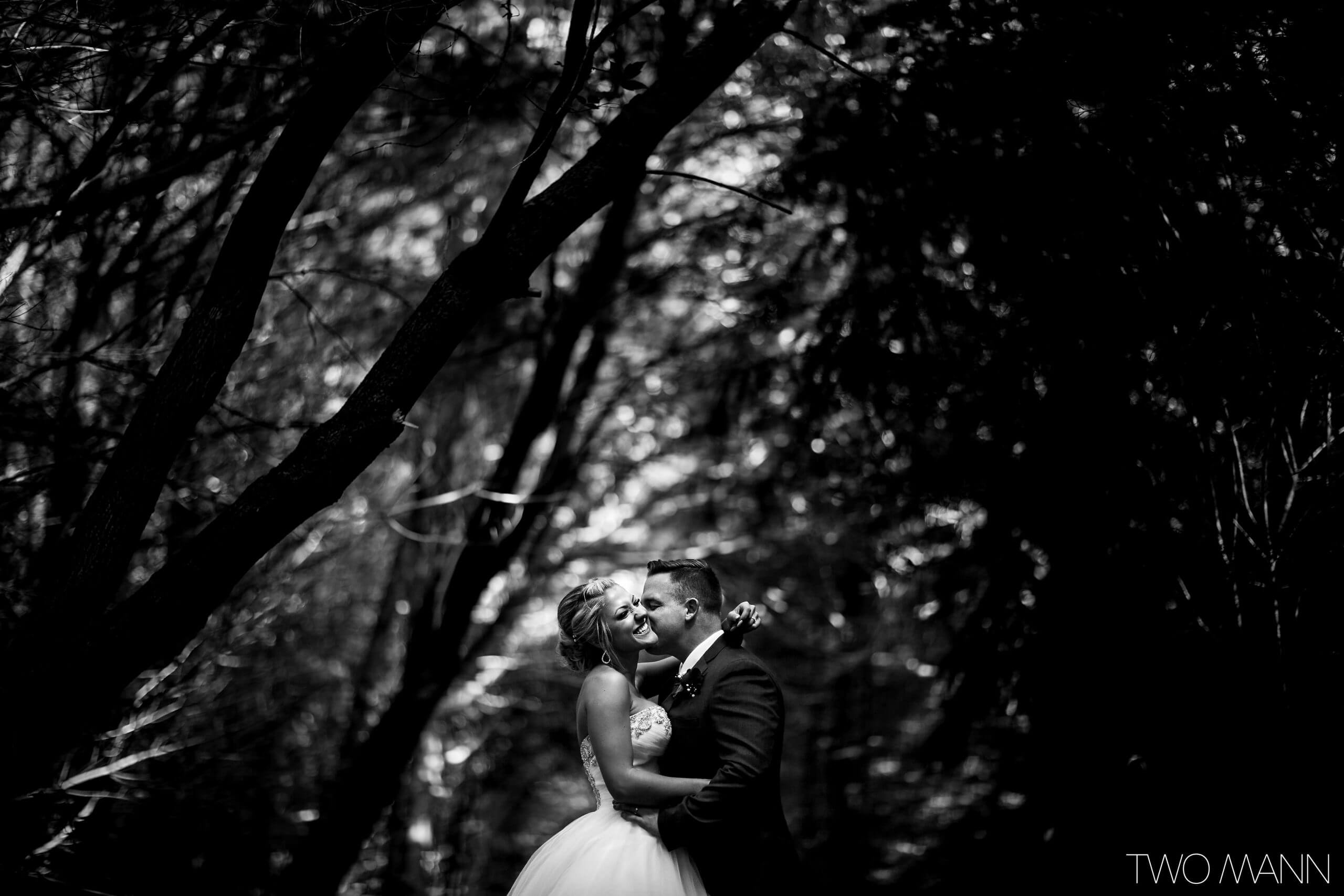 a groom kissing his bride on the cheek in the woods in Paris Ontario