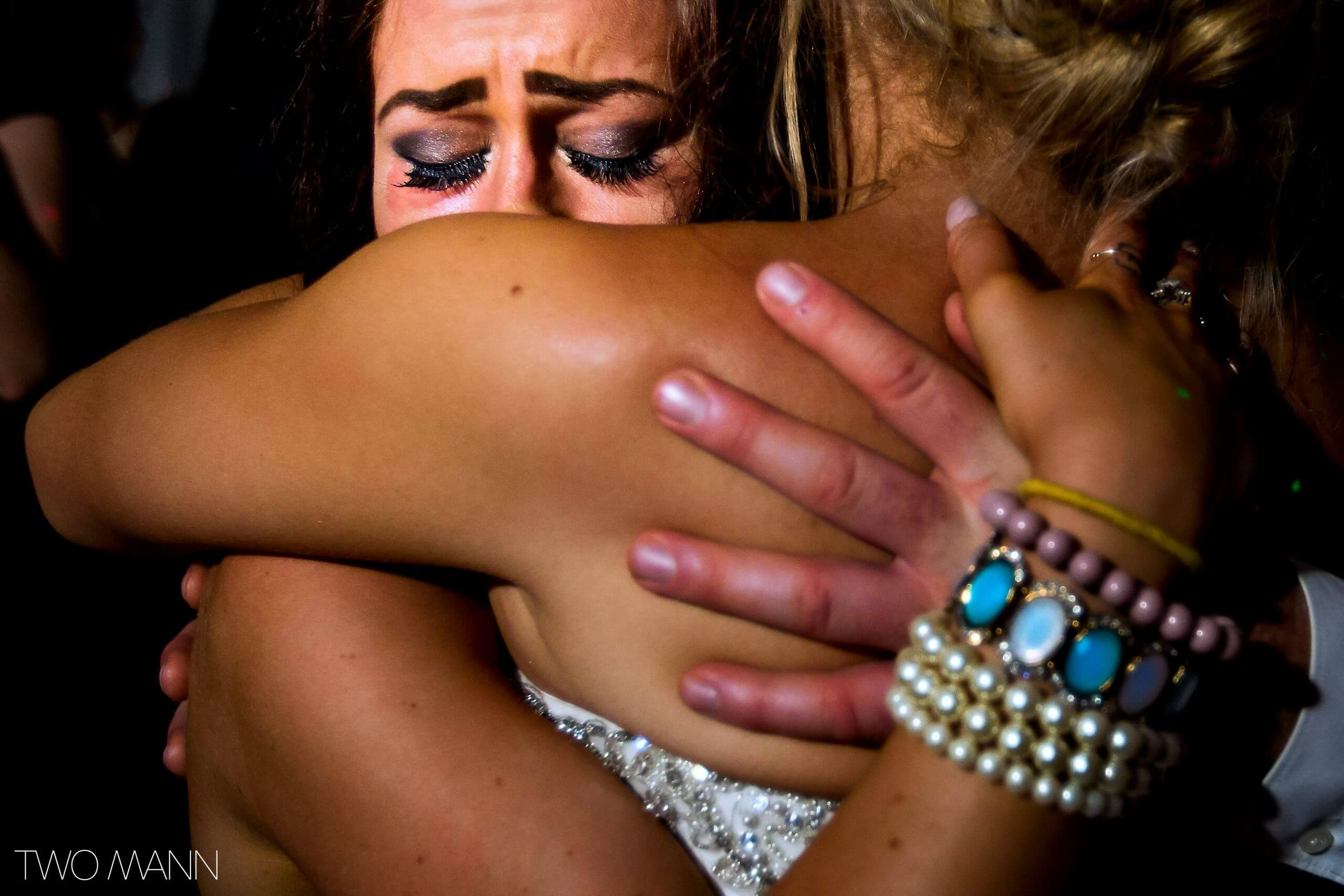 a bride hugging emotionally with a friend at reception