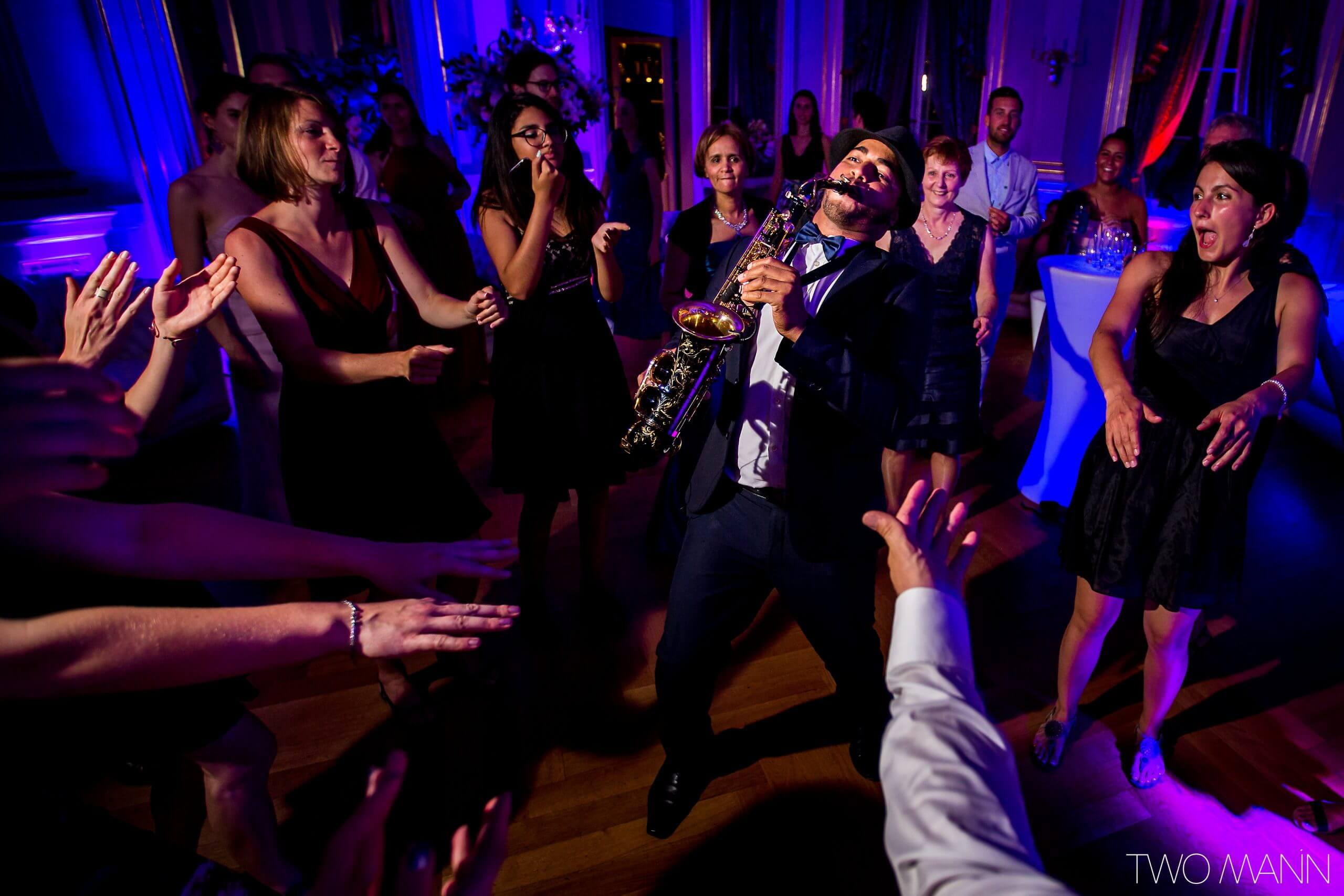 guests cheering at a saxophonist at a wedding reception