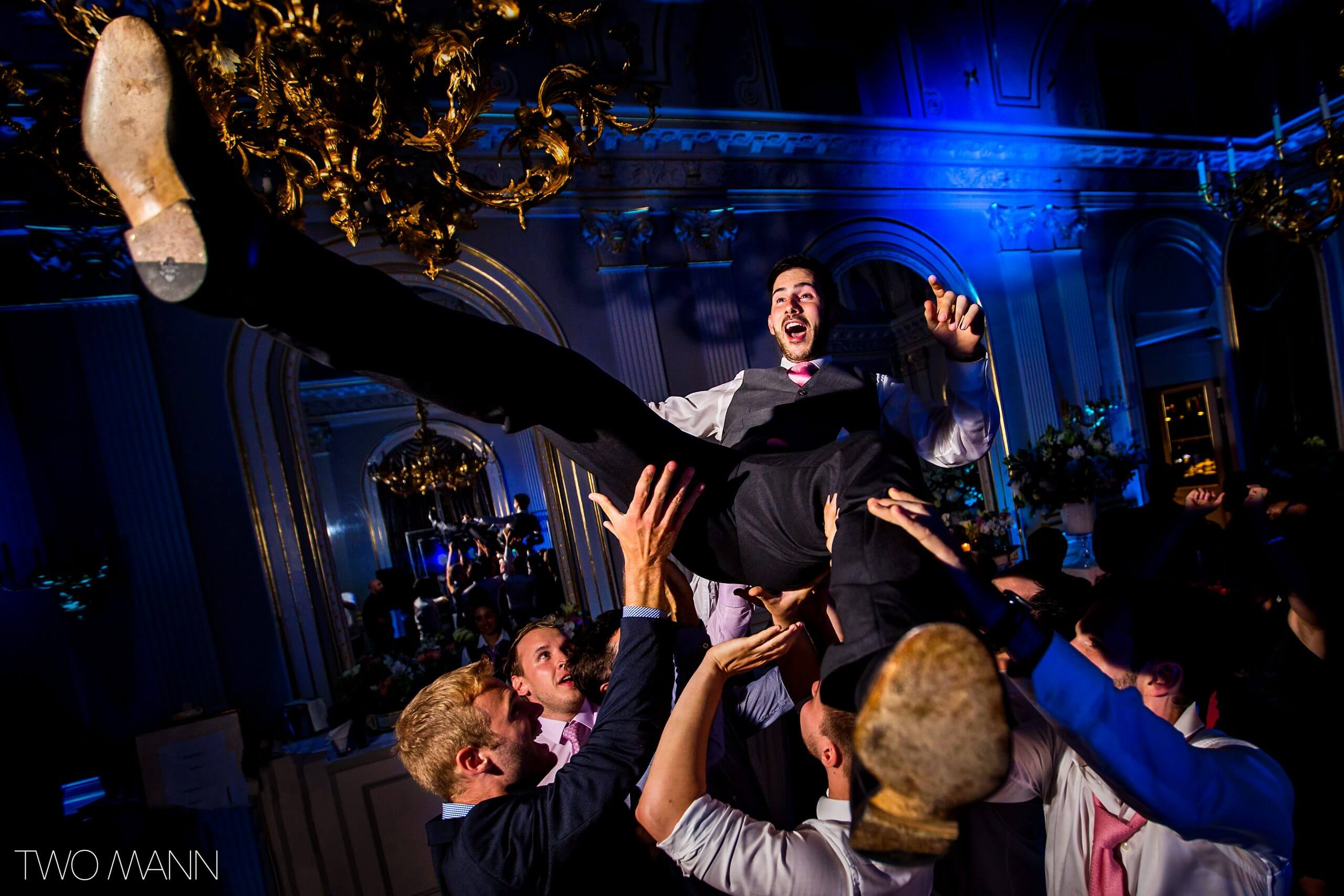 friends hold up a groom at a wedding reception