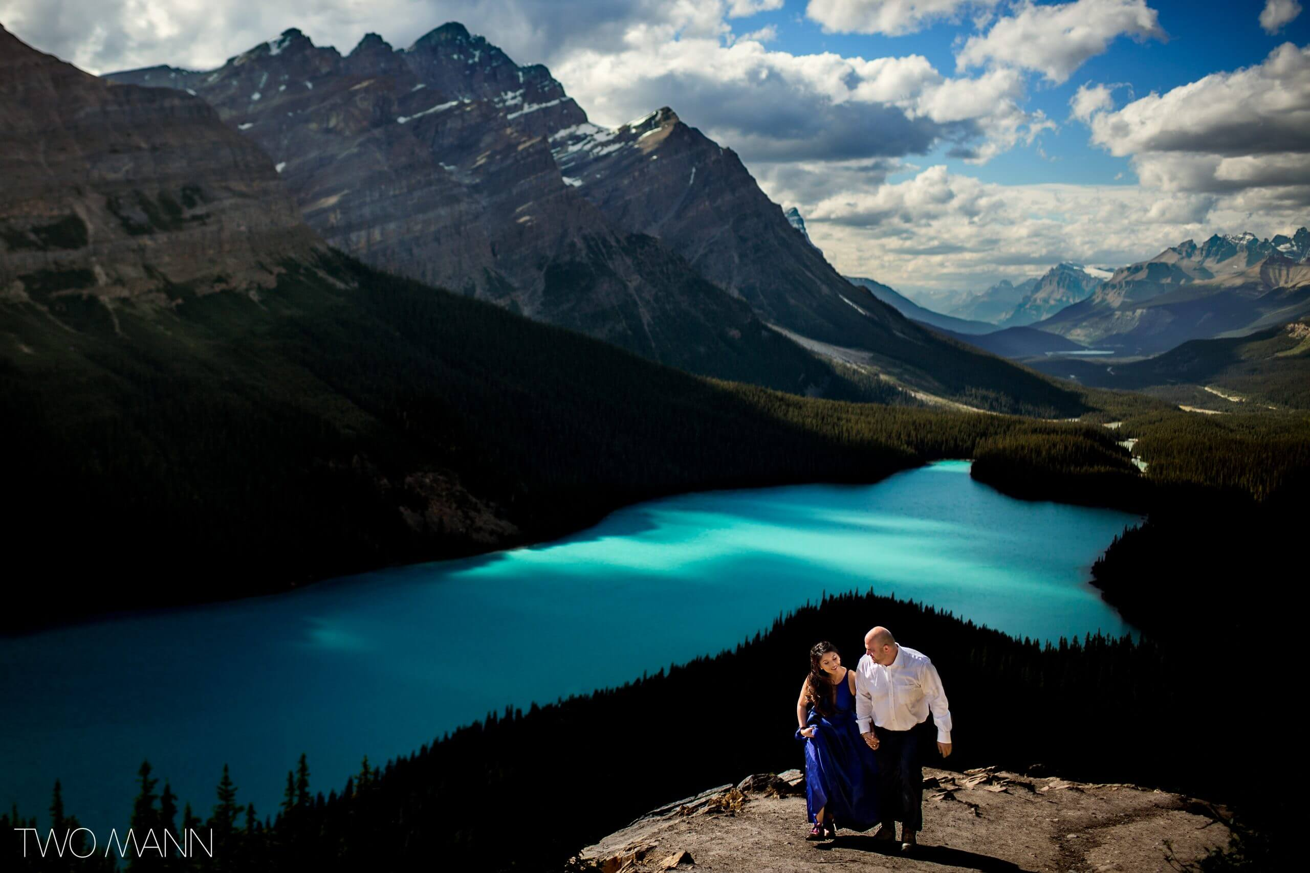 bride and groom with lake and mountain in the background