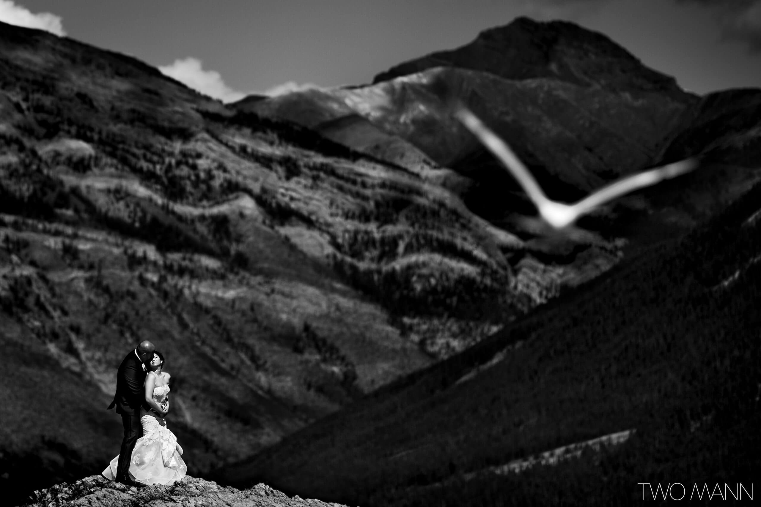 bride and groom embracing with Canadian Rockies in the background