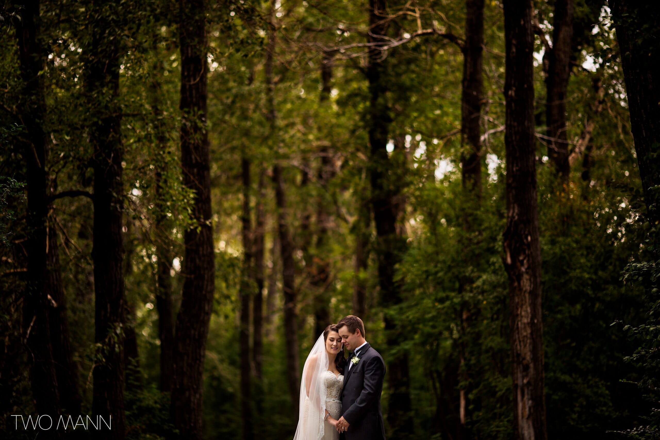 bride and groom embracing on a background of forest