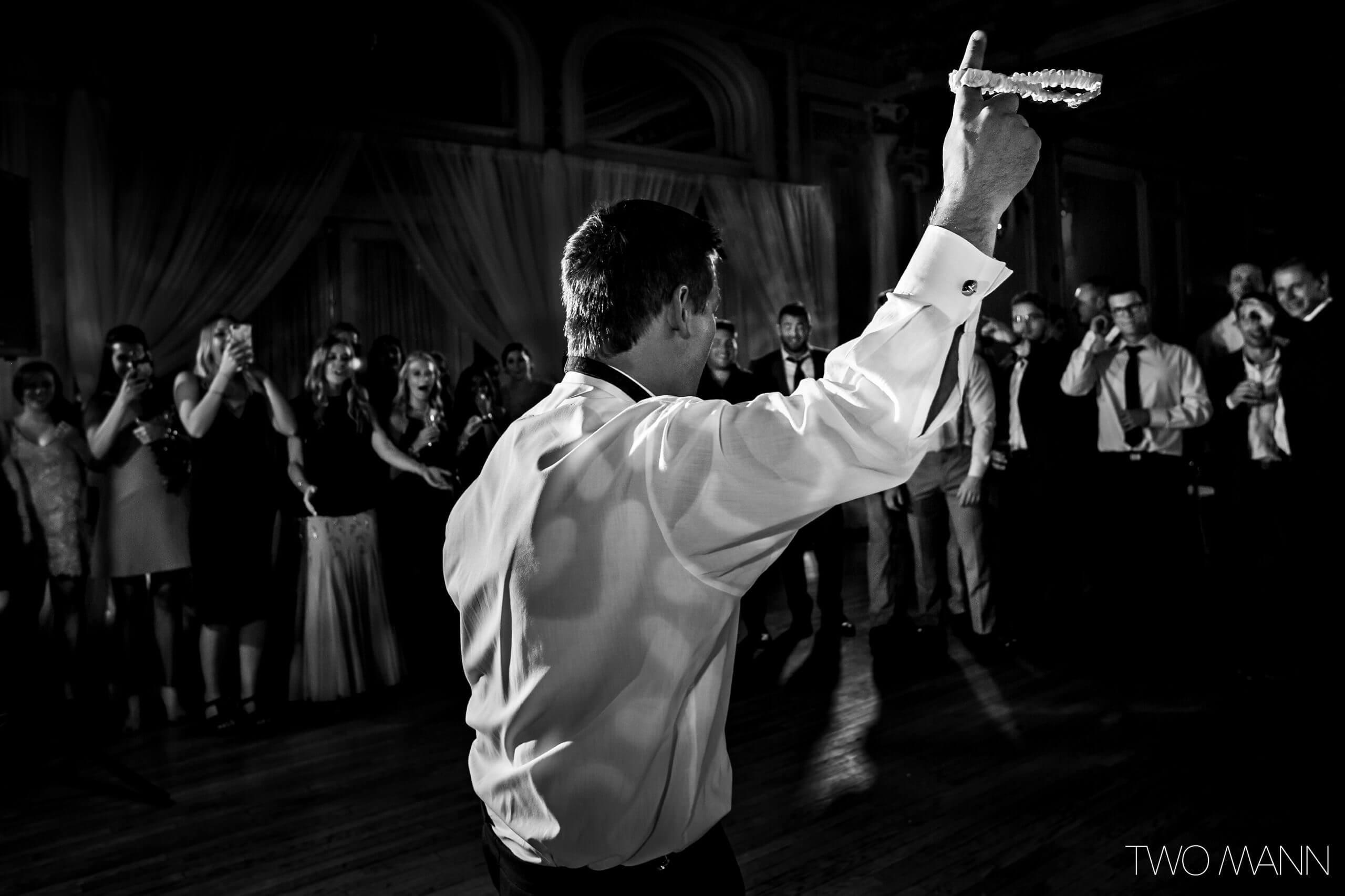guests cheer the groom on his dance