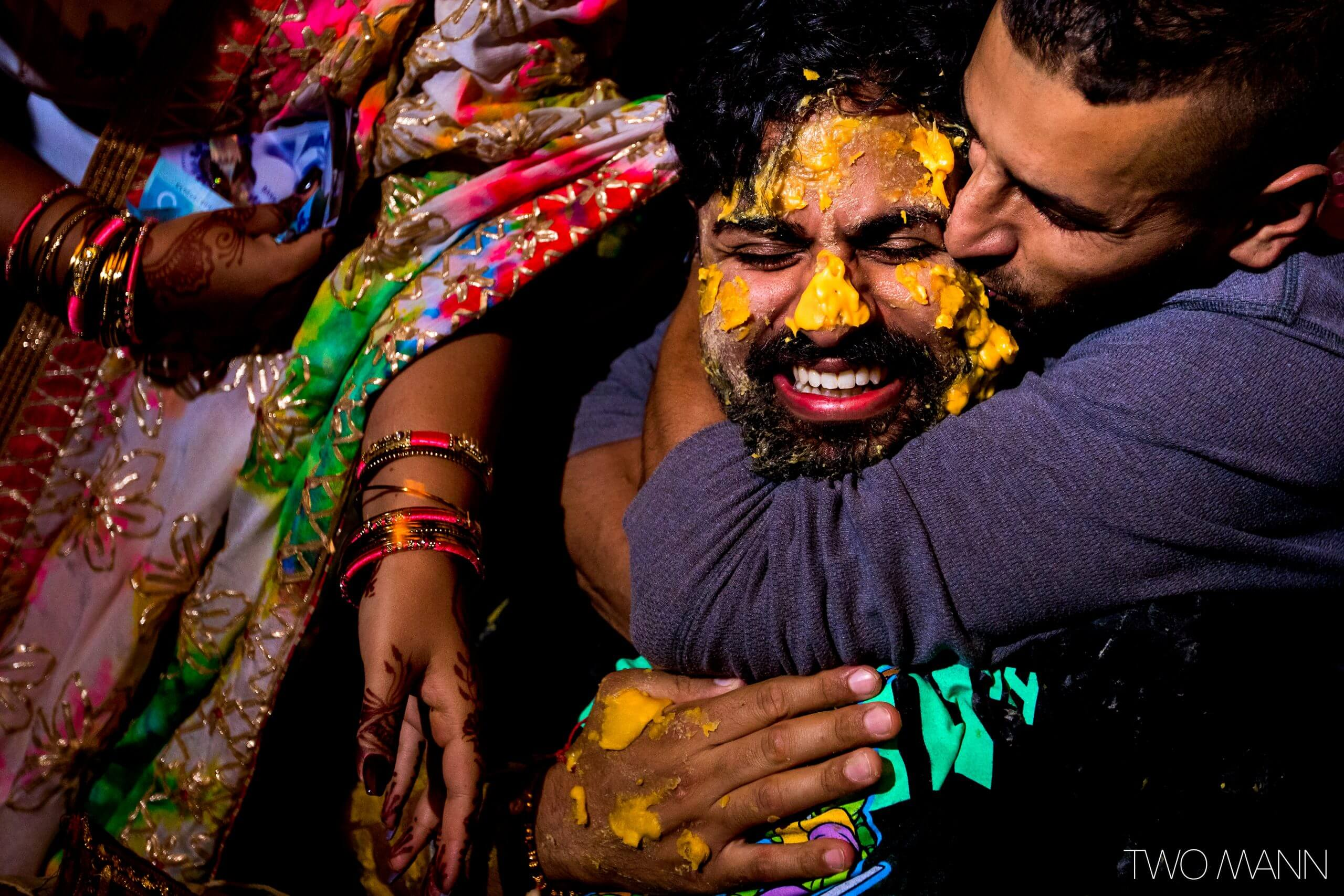a friend giving warm hug to indian groom