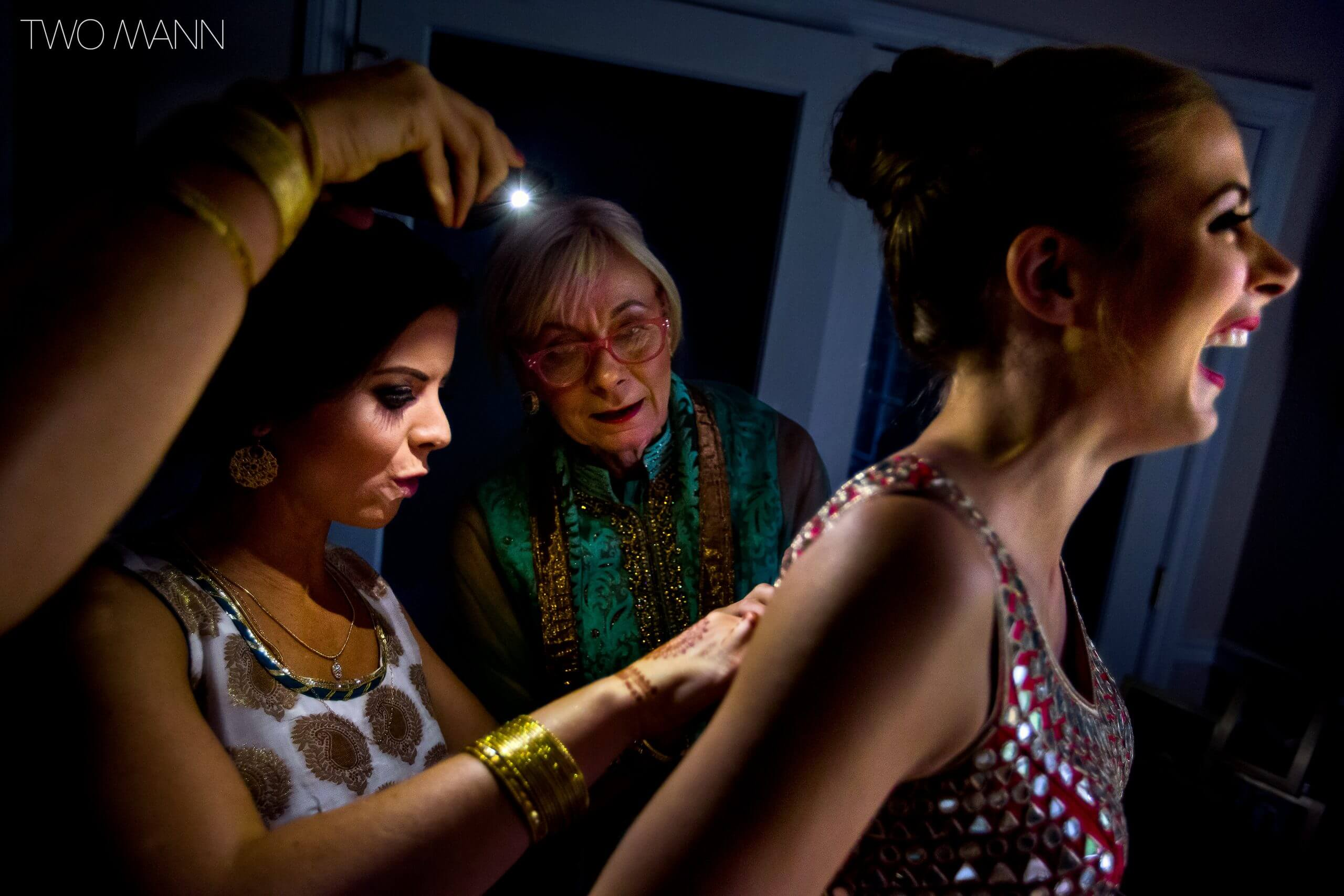 friends helping an Indian bride to put on her dress