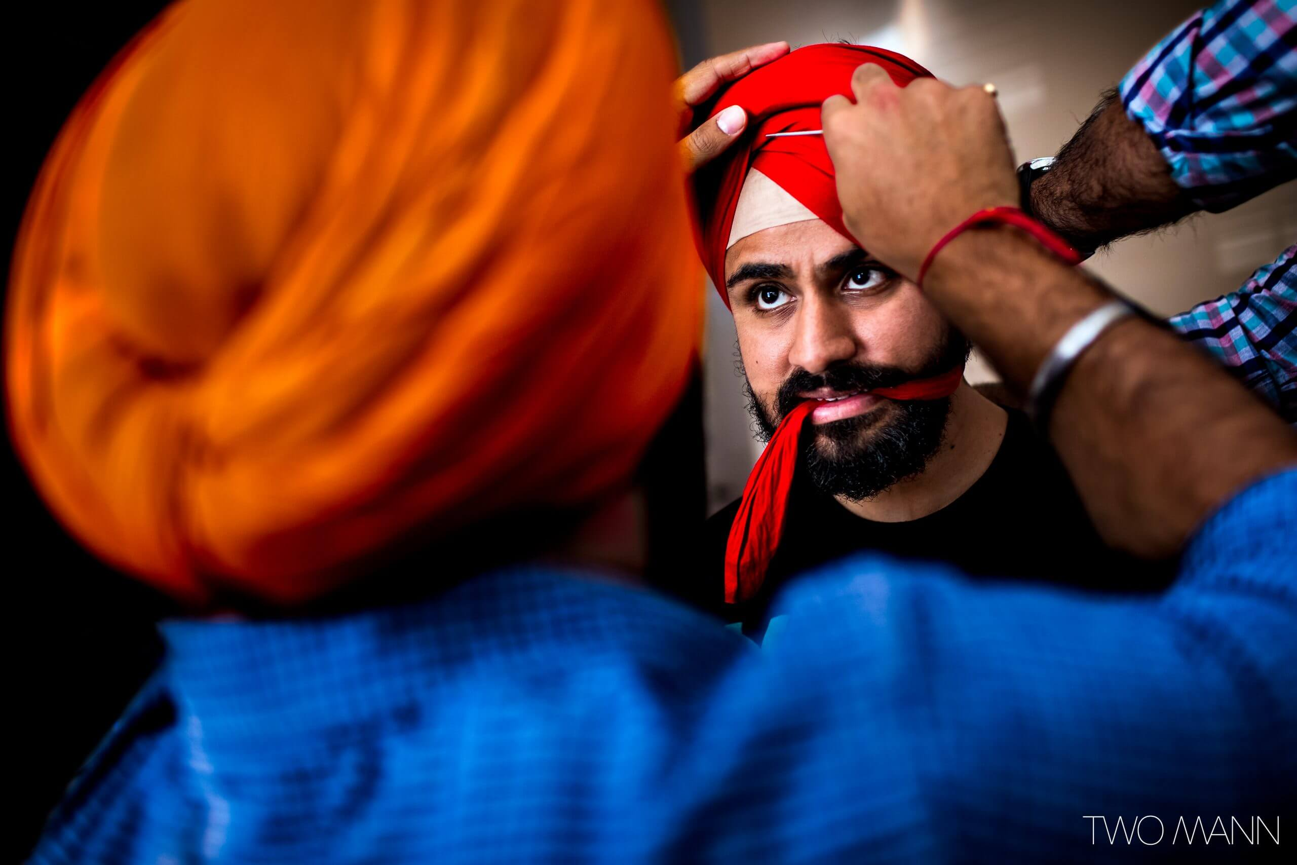 friends helping an Indian groom with his wedding turban