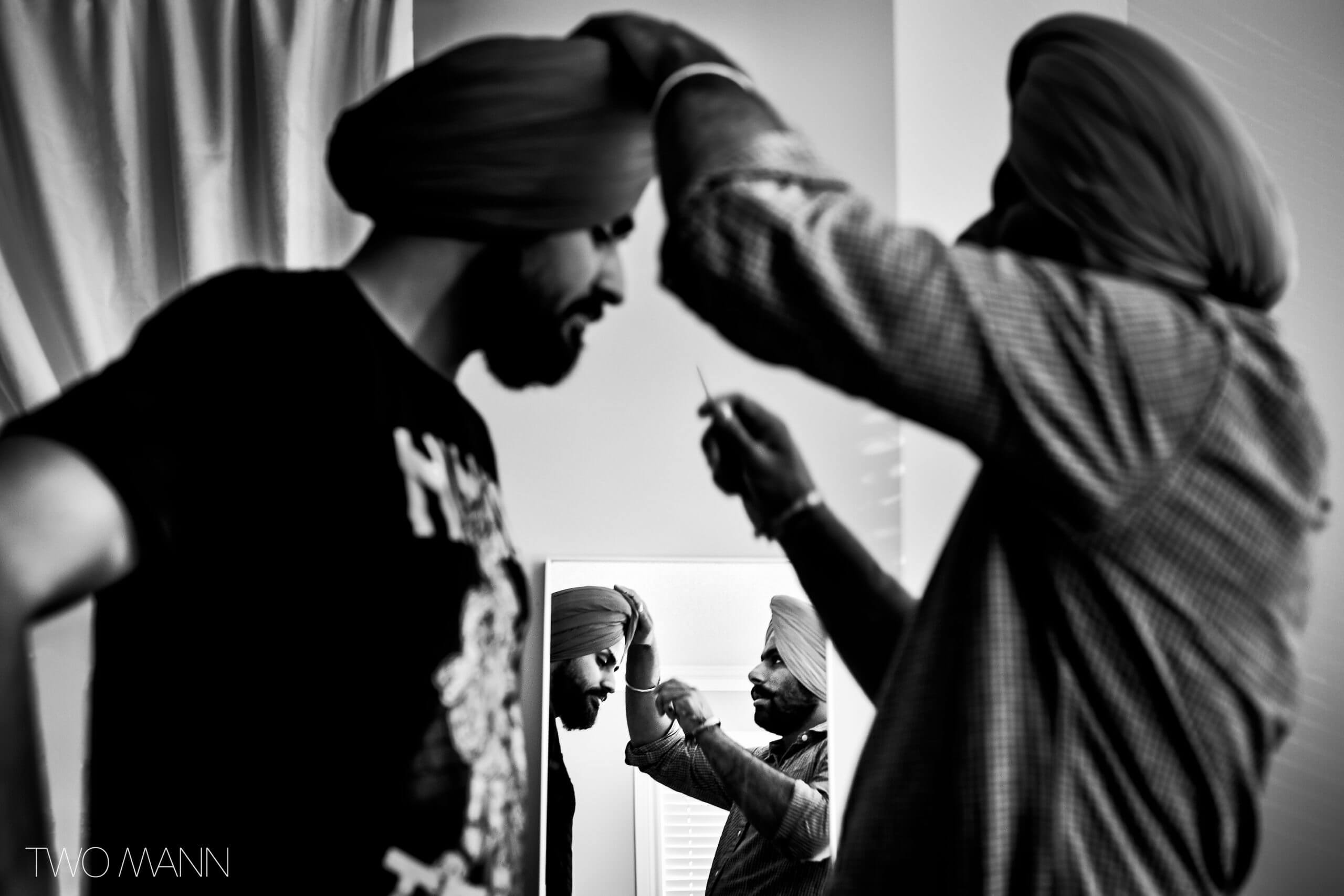 a friend helping an Indian groom with his wedding turban