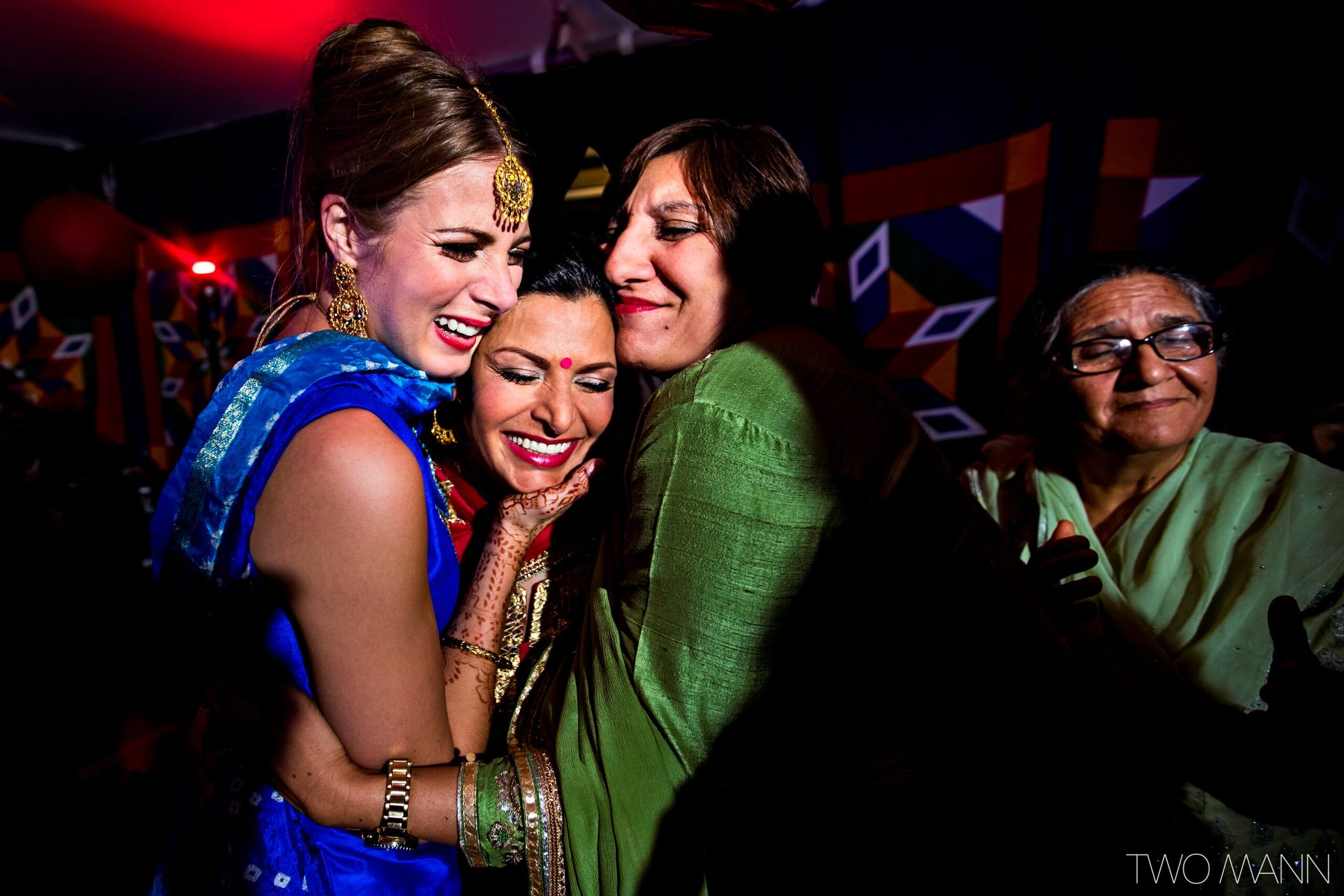 a bride hugging with friends at an indian wedding reception