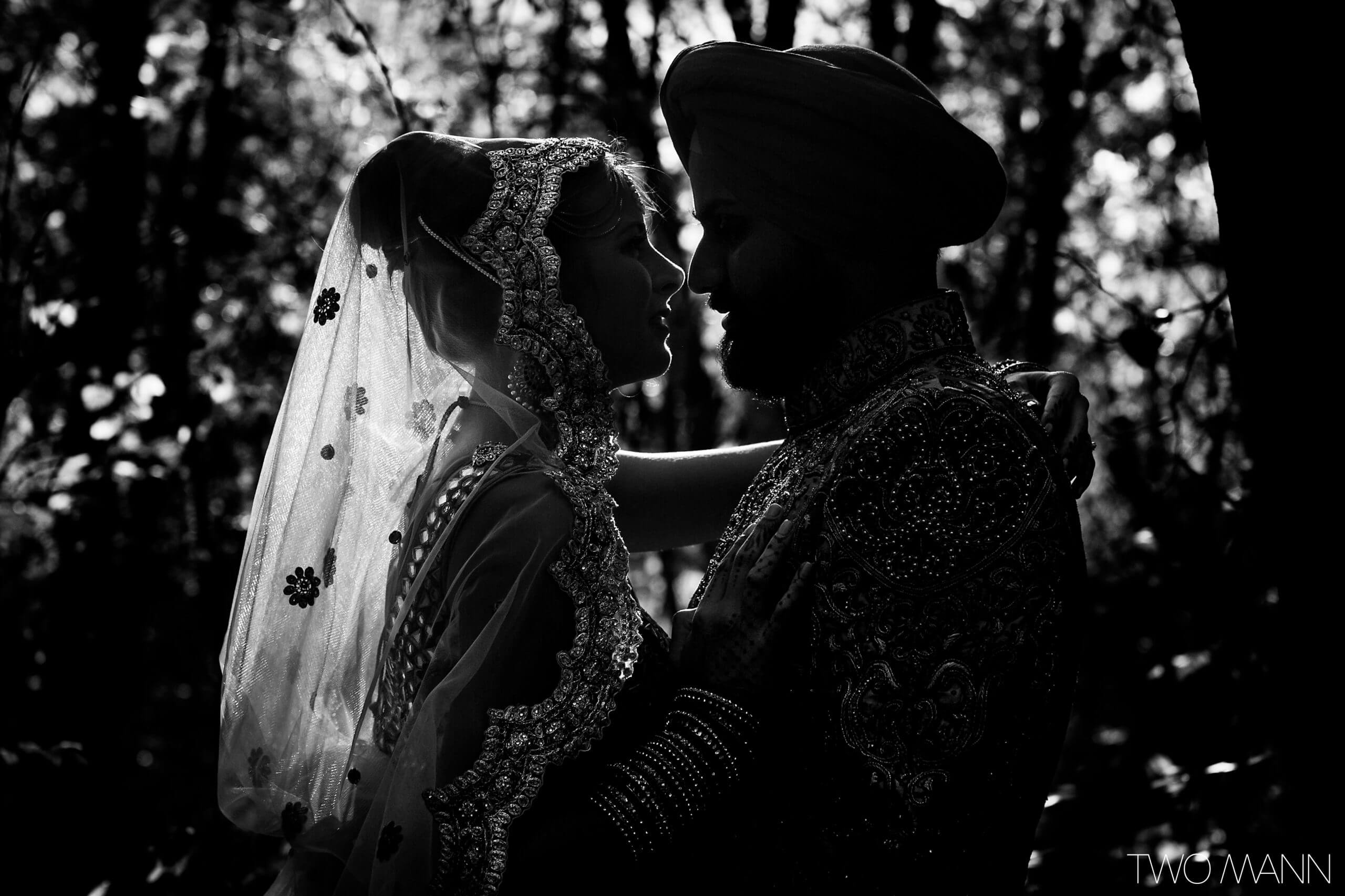 indian bride and groom embracing in traditional attires