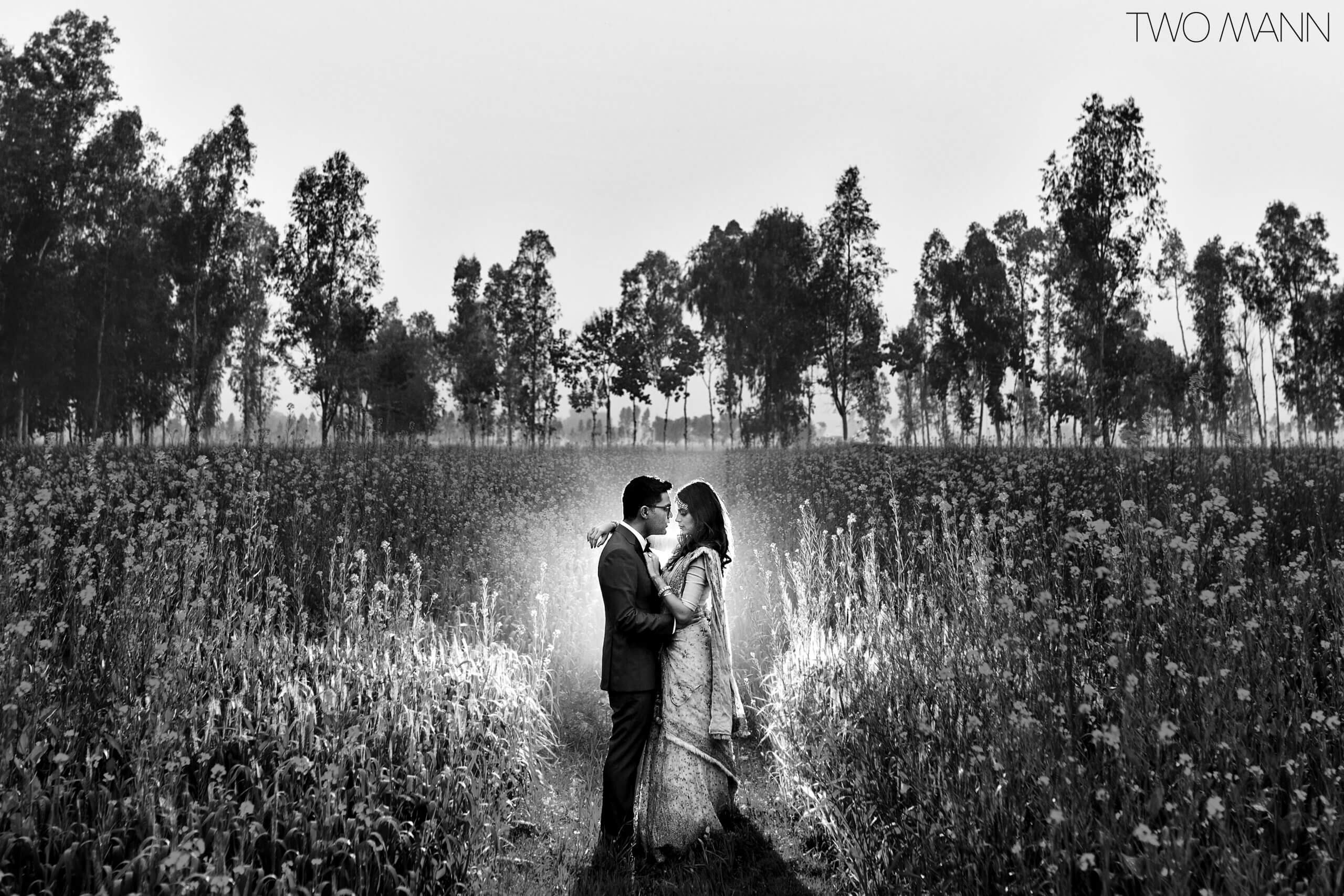 indian bride and groom embracing in the field at dawn