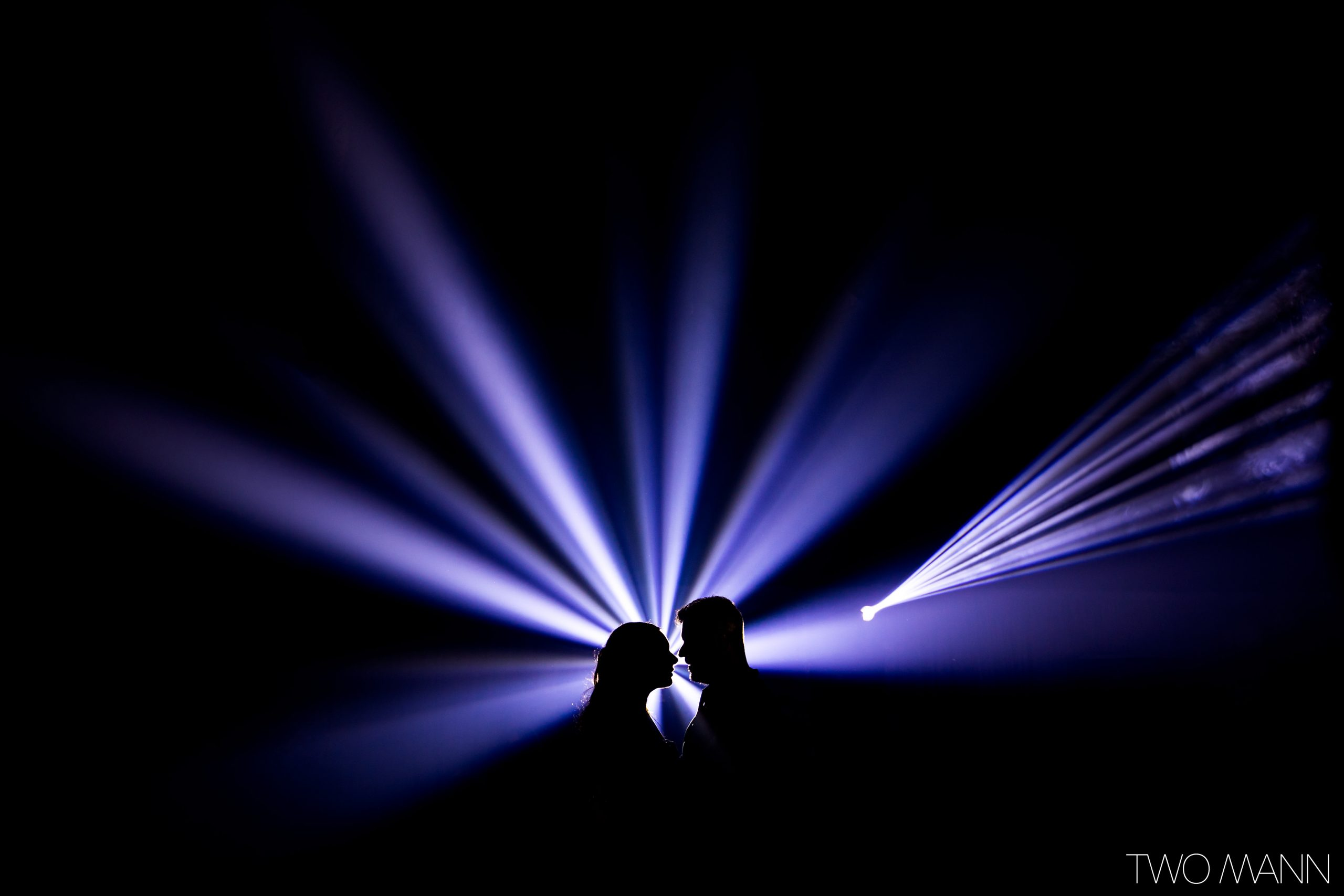 silhouette of bride and groom with dj lights at wedding reception