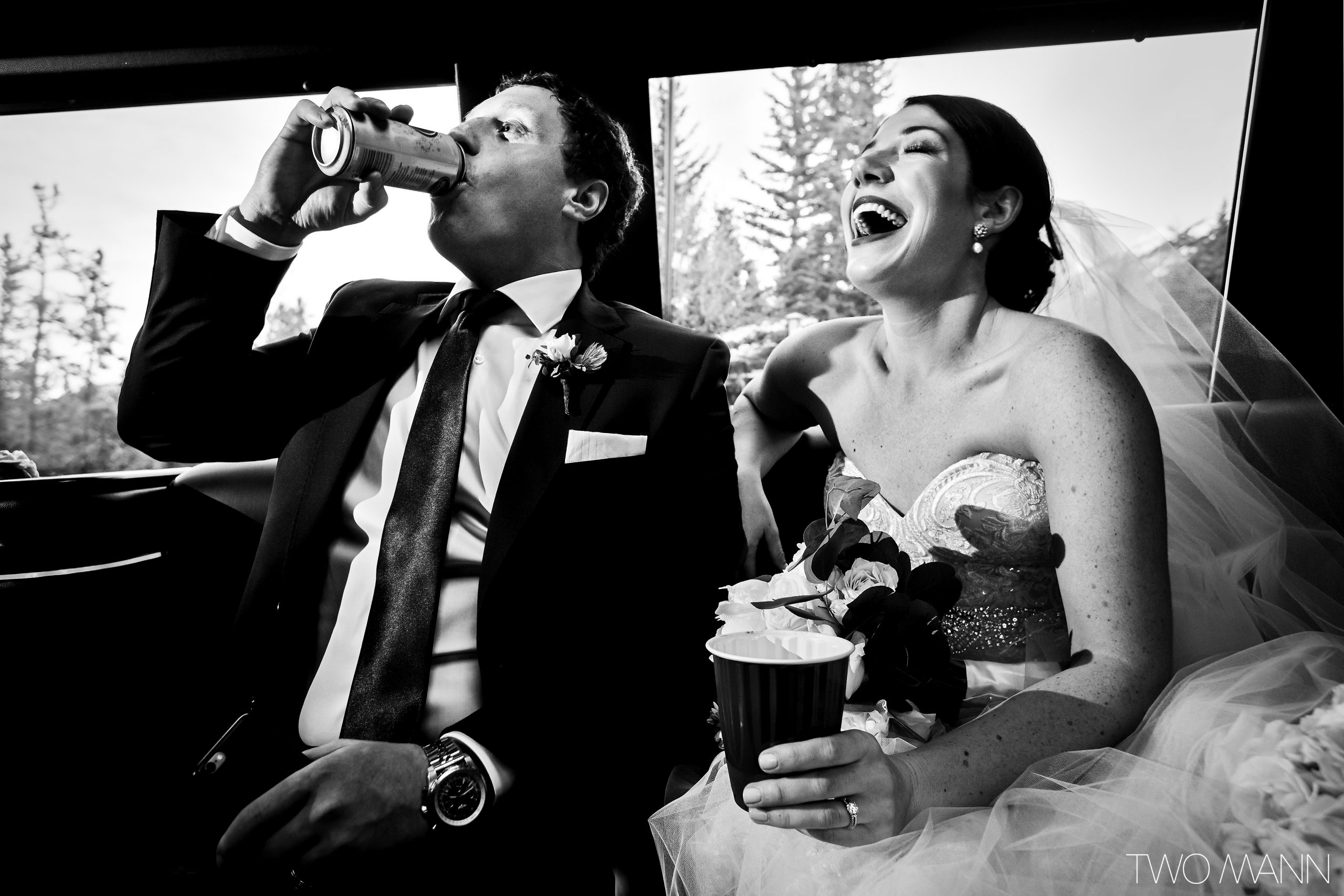 bride laughing and groom drinking beer in limo