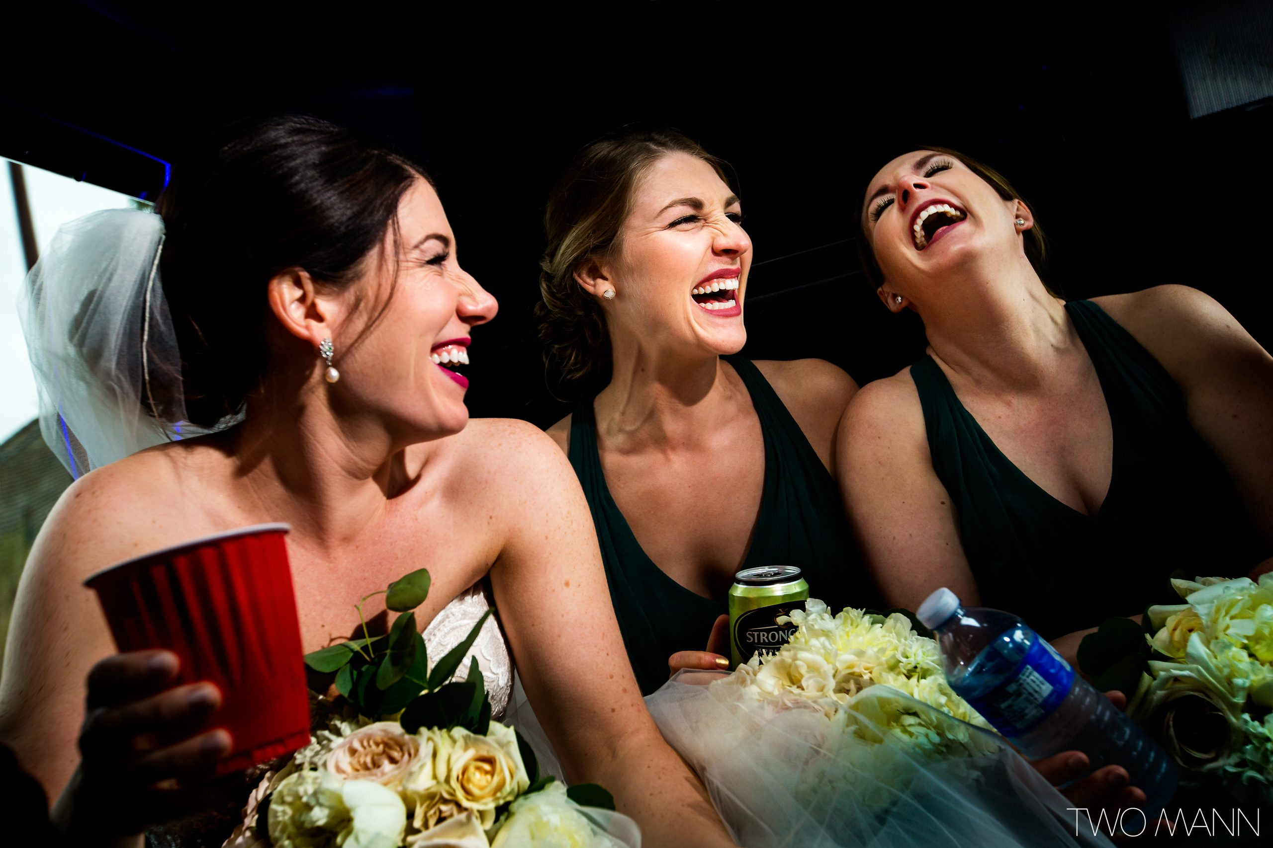 Bride and bridesmaids laughing in limo