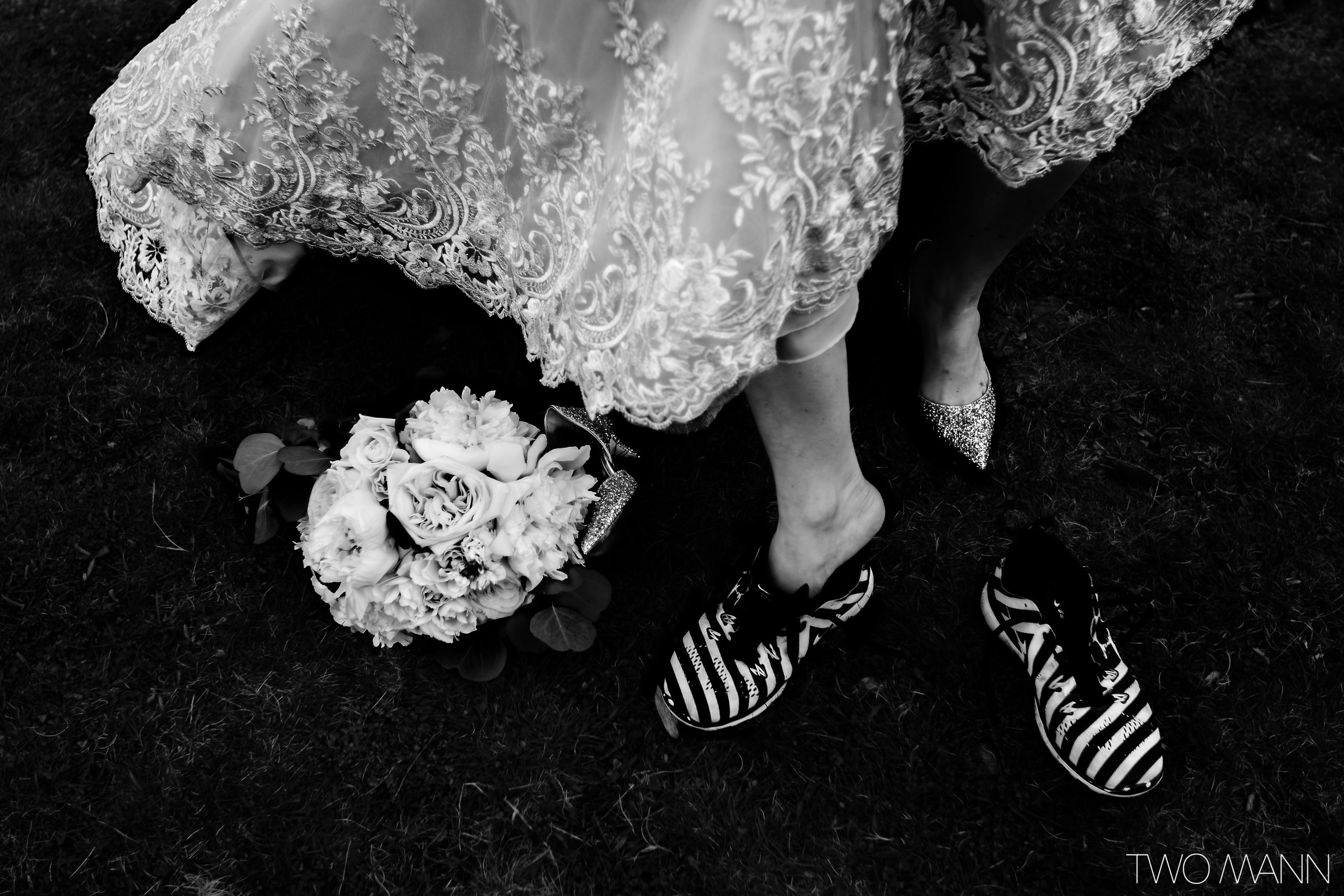 bride slipping feet into running shoes with bouquet at mountain wedding
