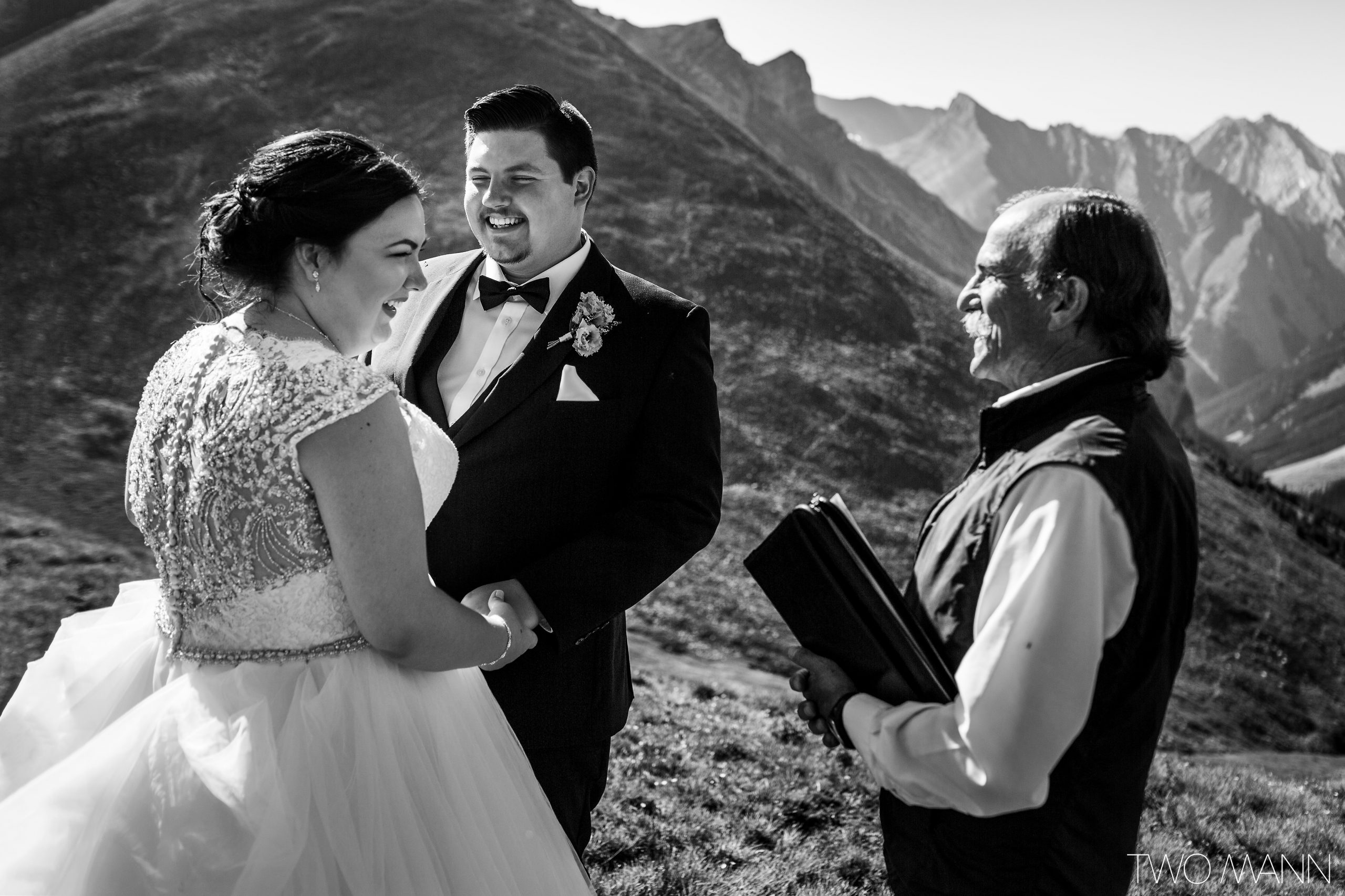bride and groom and wedding commissioner in mountains during heli-elopement ceremony with laughter