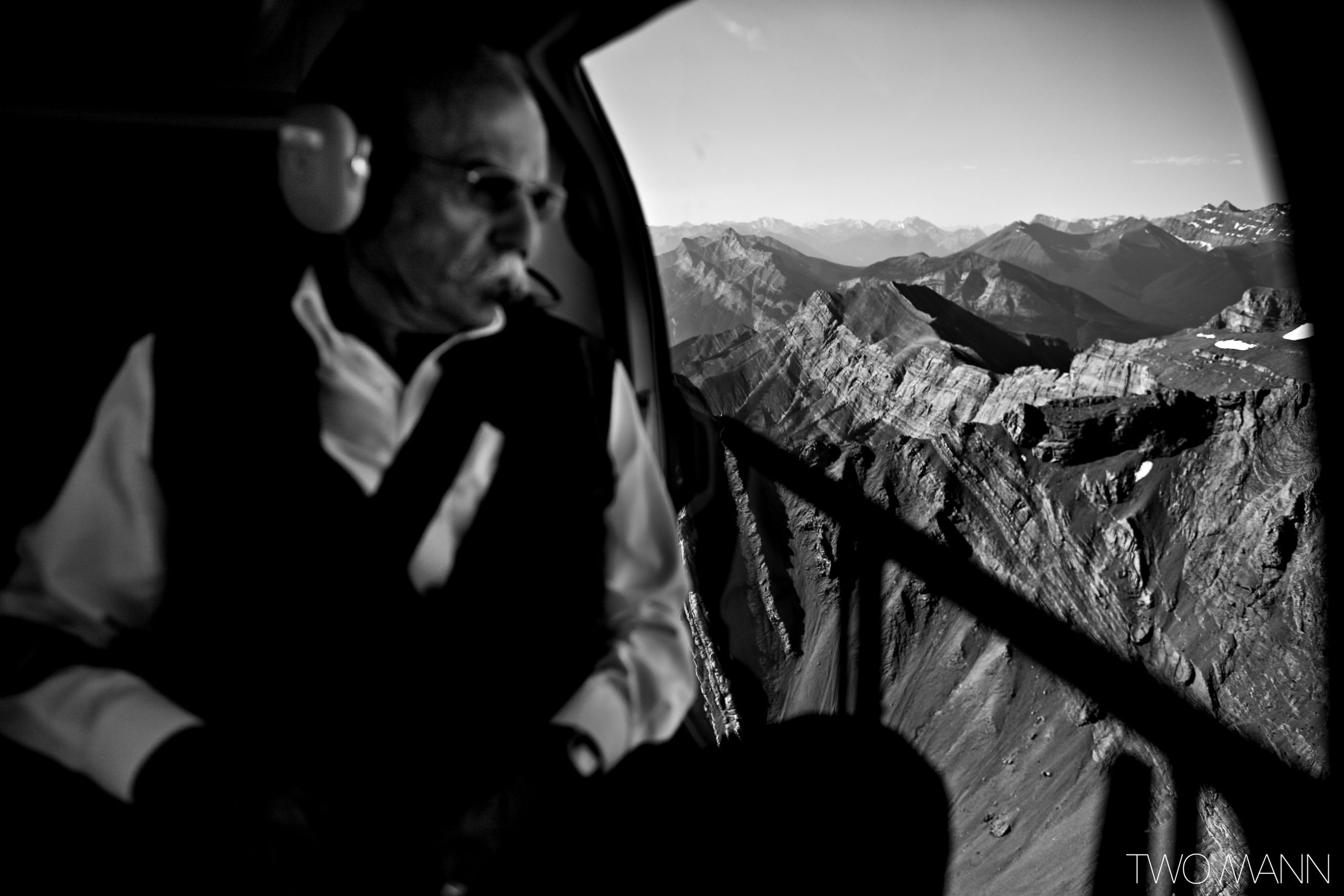 wedding commissioner looking out window of helicopter on way to heli-elopement ceremony in mountains