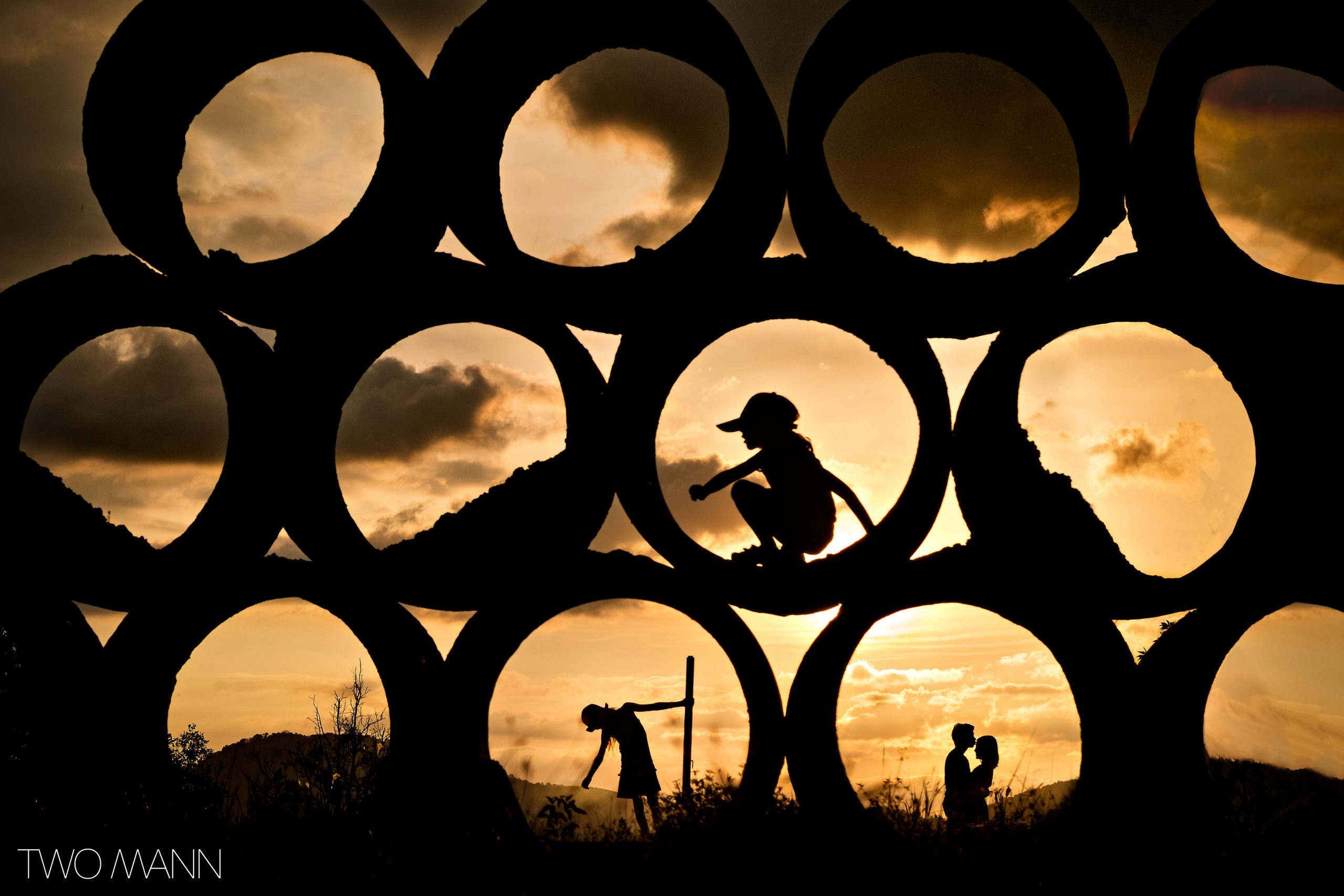 Couple in love kissing with kids playing on construction site silhouetted at sunset in Thailand.