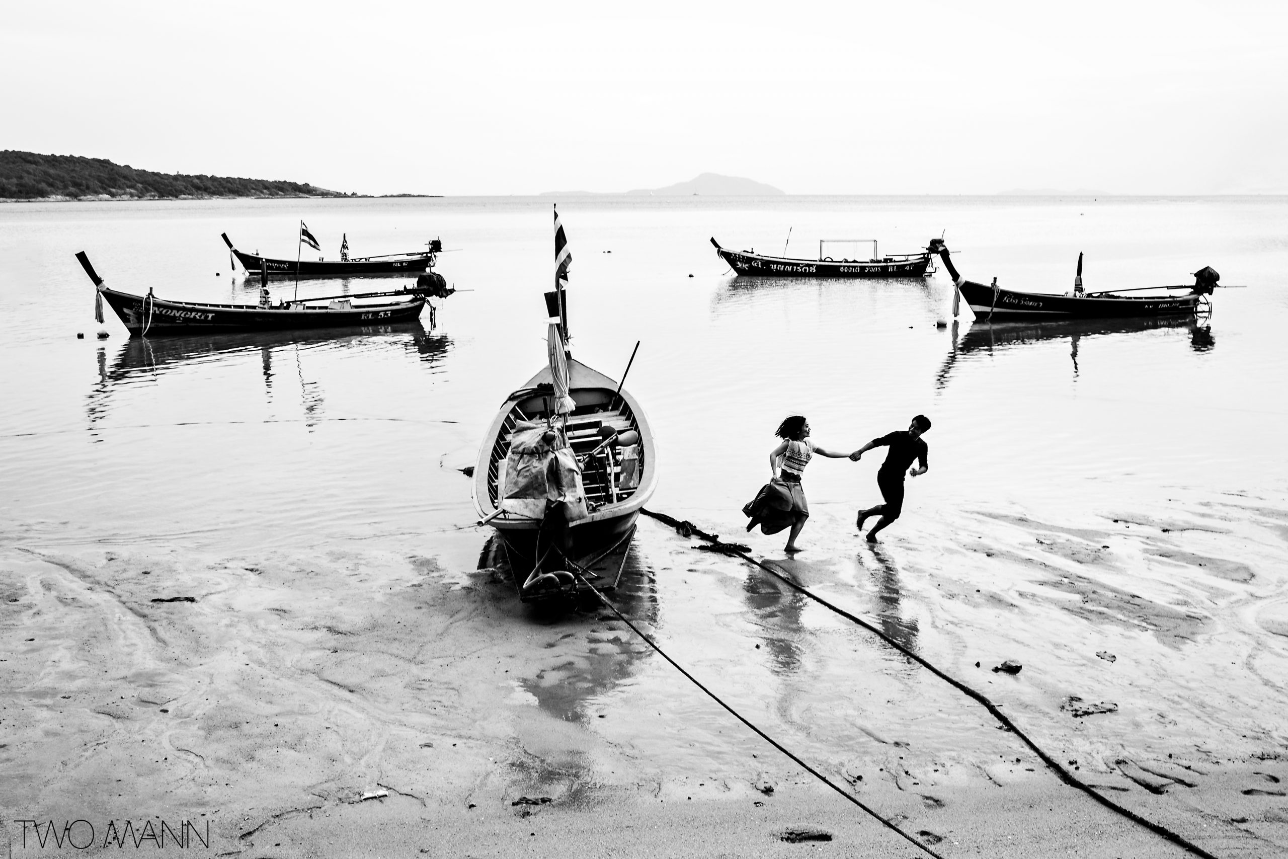 Black and white photo of married couple holding hands and running along a beach with long boats in Thailand.