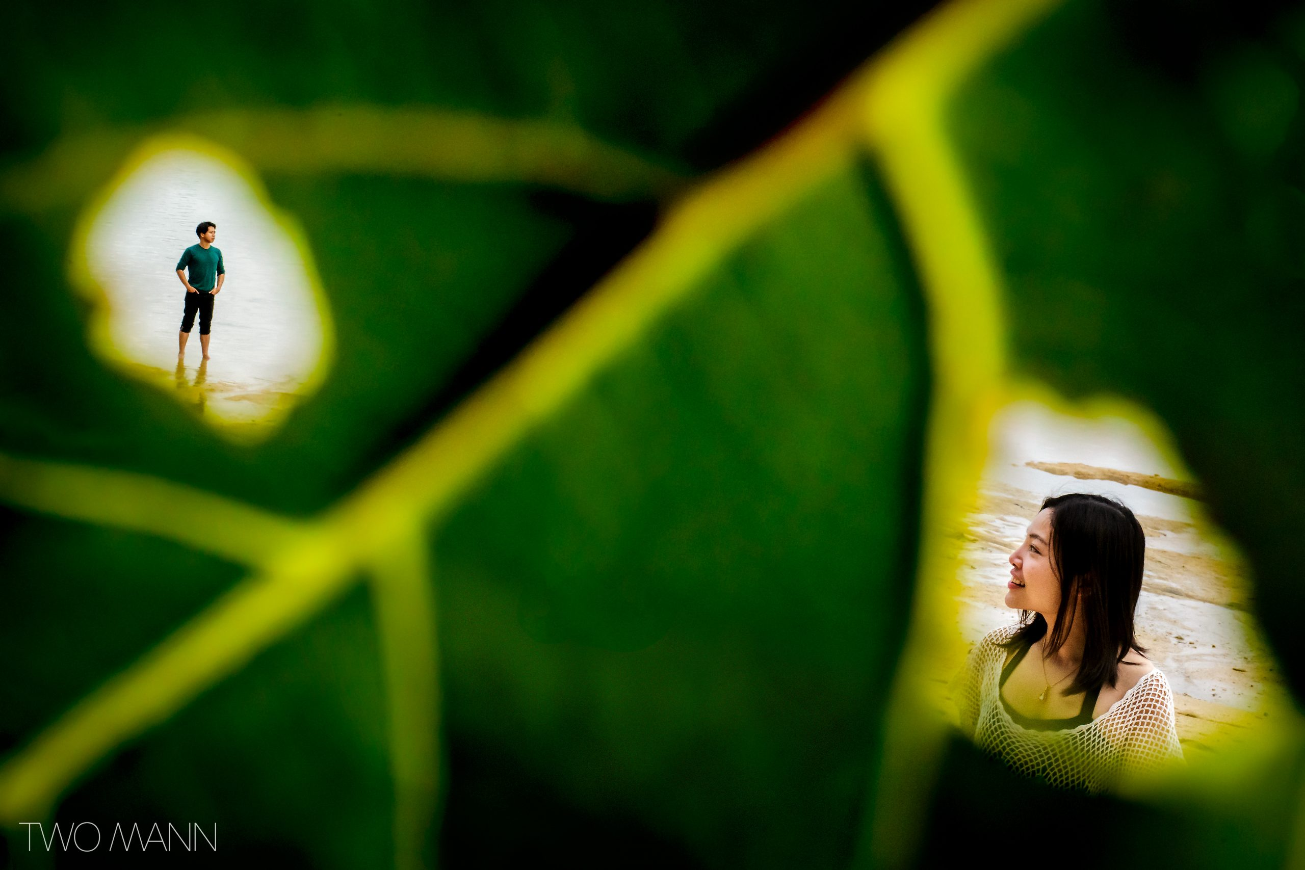 Photo of man and woman in love on beach through green leaf in Thailand.