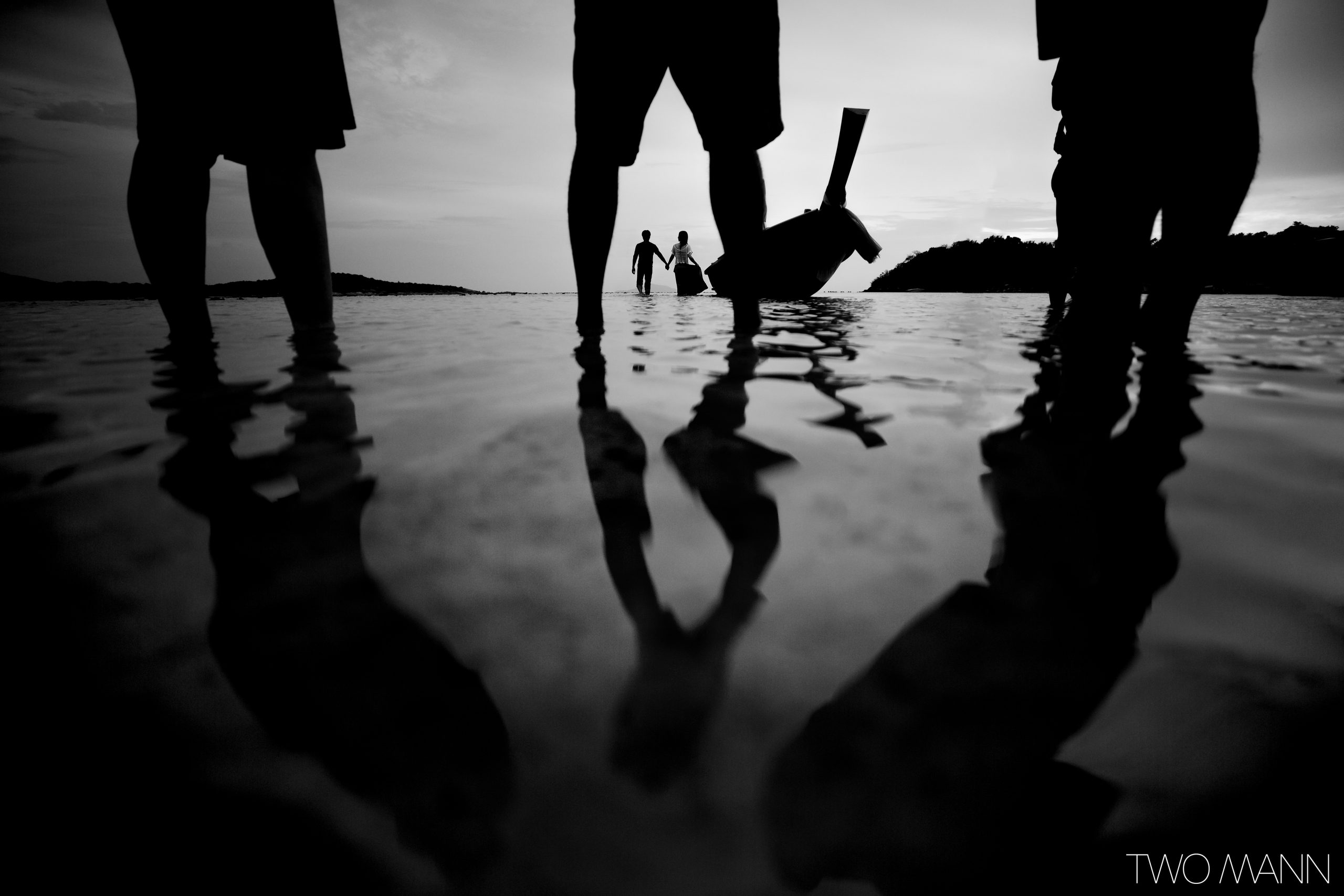 Black and white photo of a couple in love, holding hands and walking in the ocean beside long boat in Thailand, silhouetted through legs.