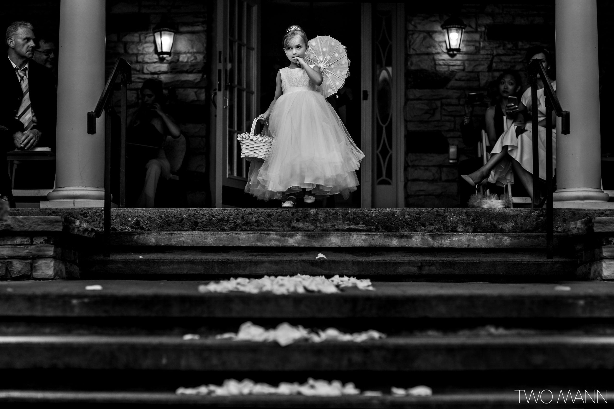Young flower girl on top of steps prepares to walk down wedding aisle