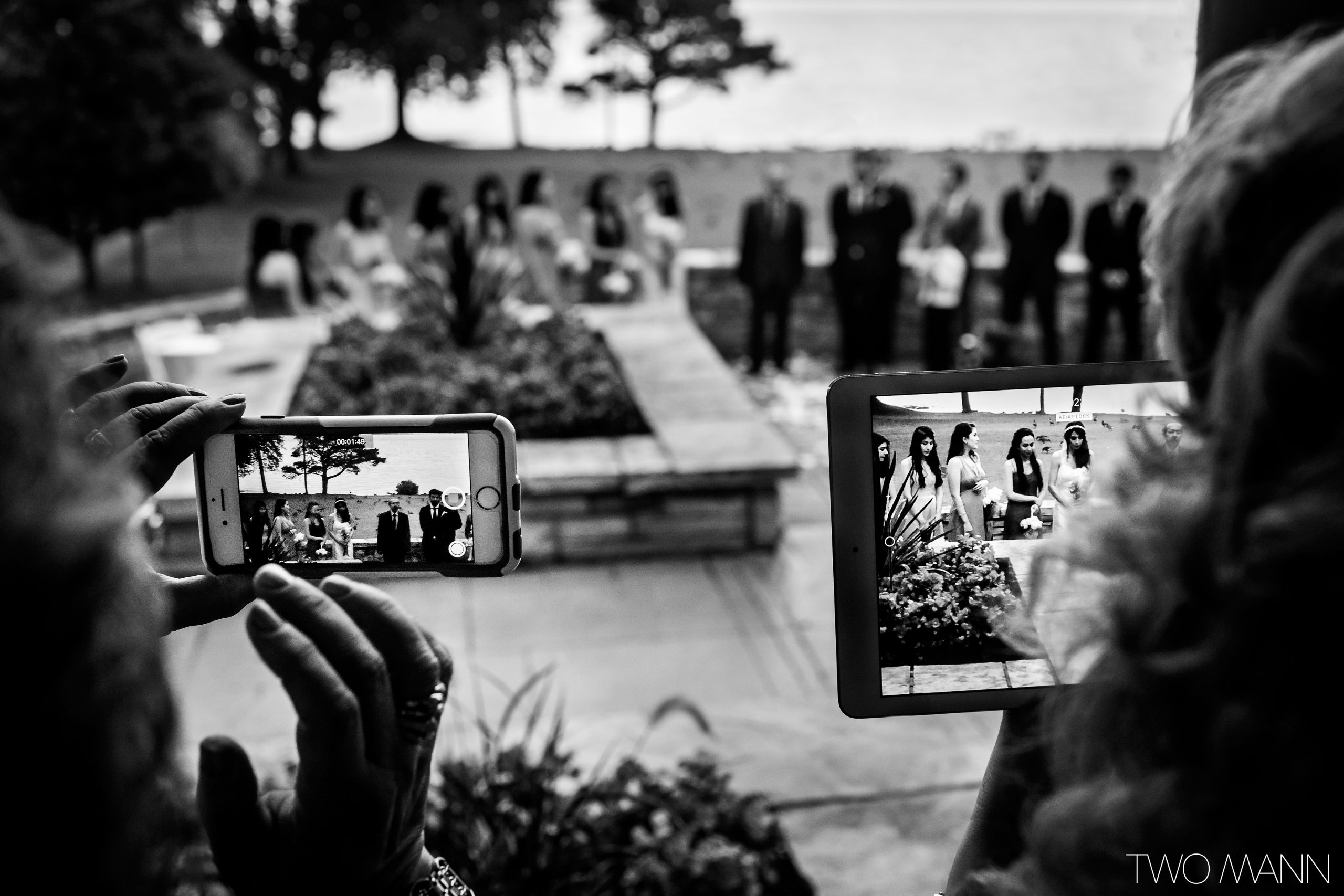 Two woman takes photos with iPhone and iPad during wedding ceremony