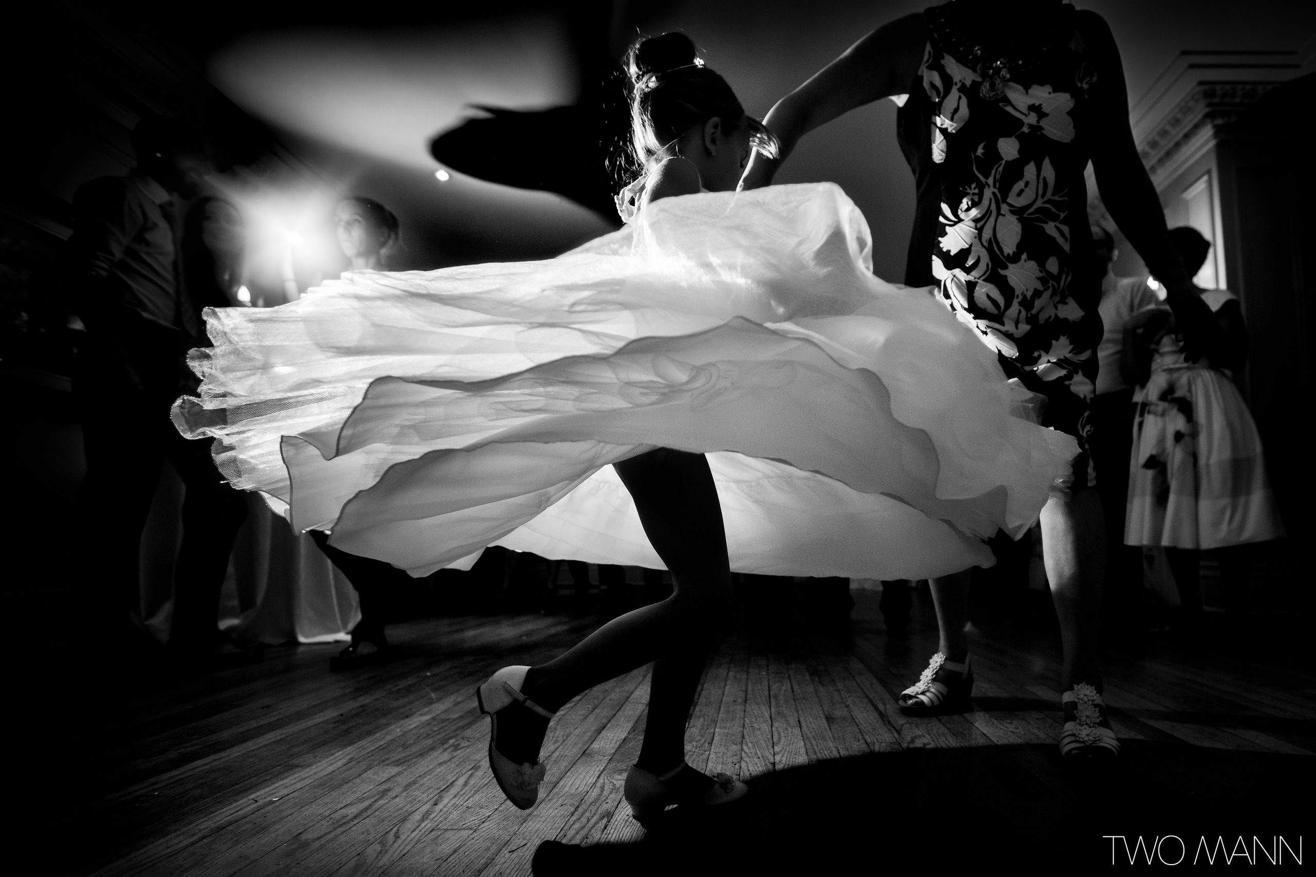 Young girl twirling on wedding dance floor in white dress