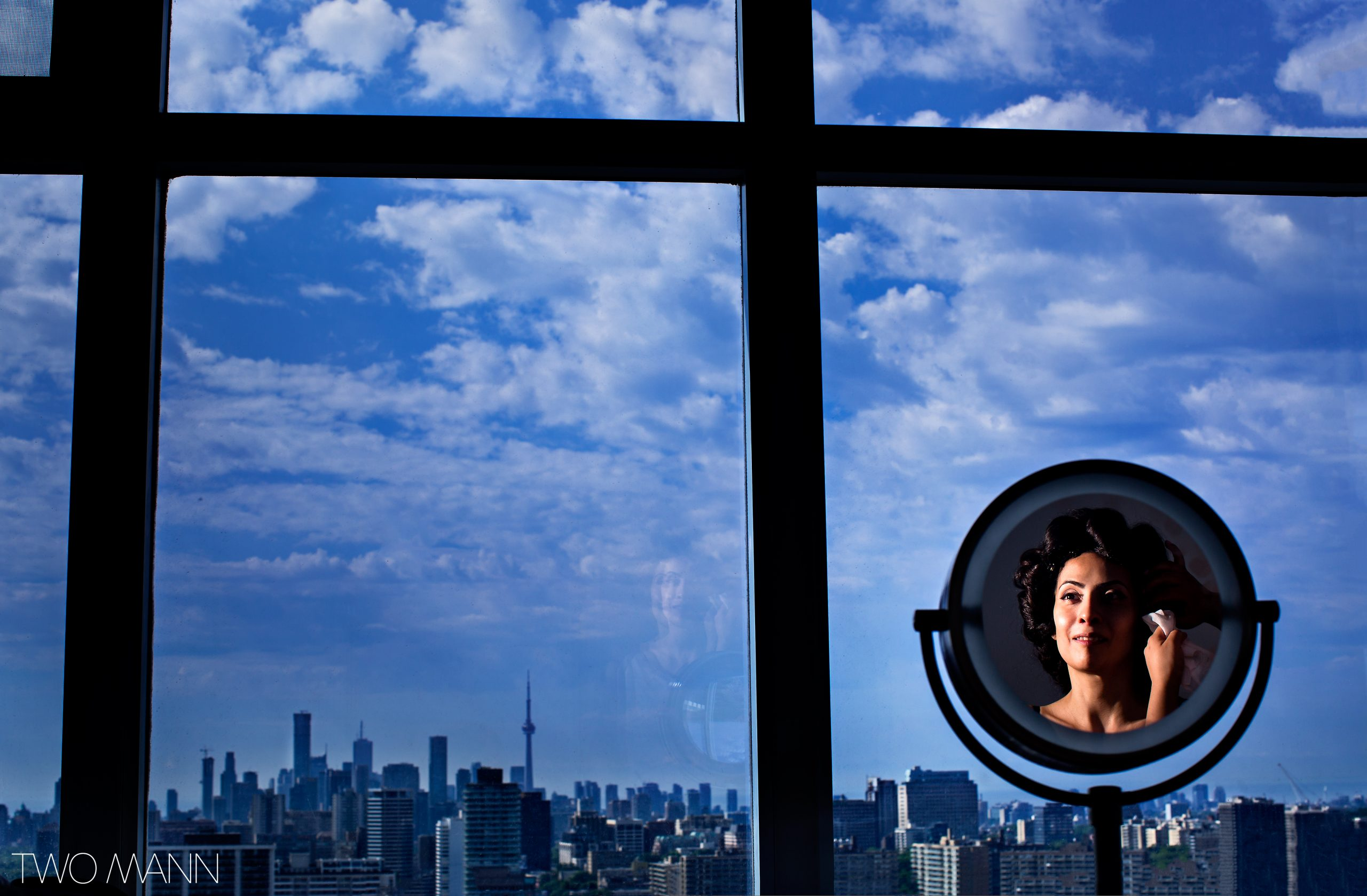 Reflection of woman doing her make up gazing at the Toronto cityscape outside her window