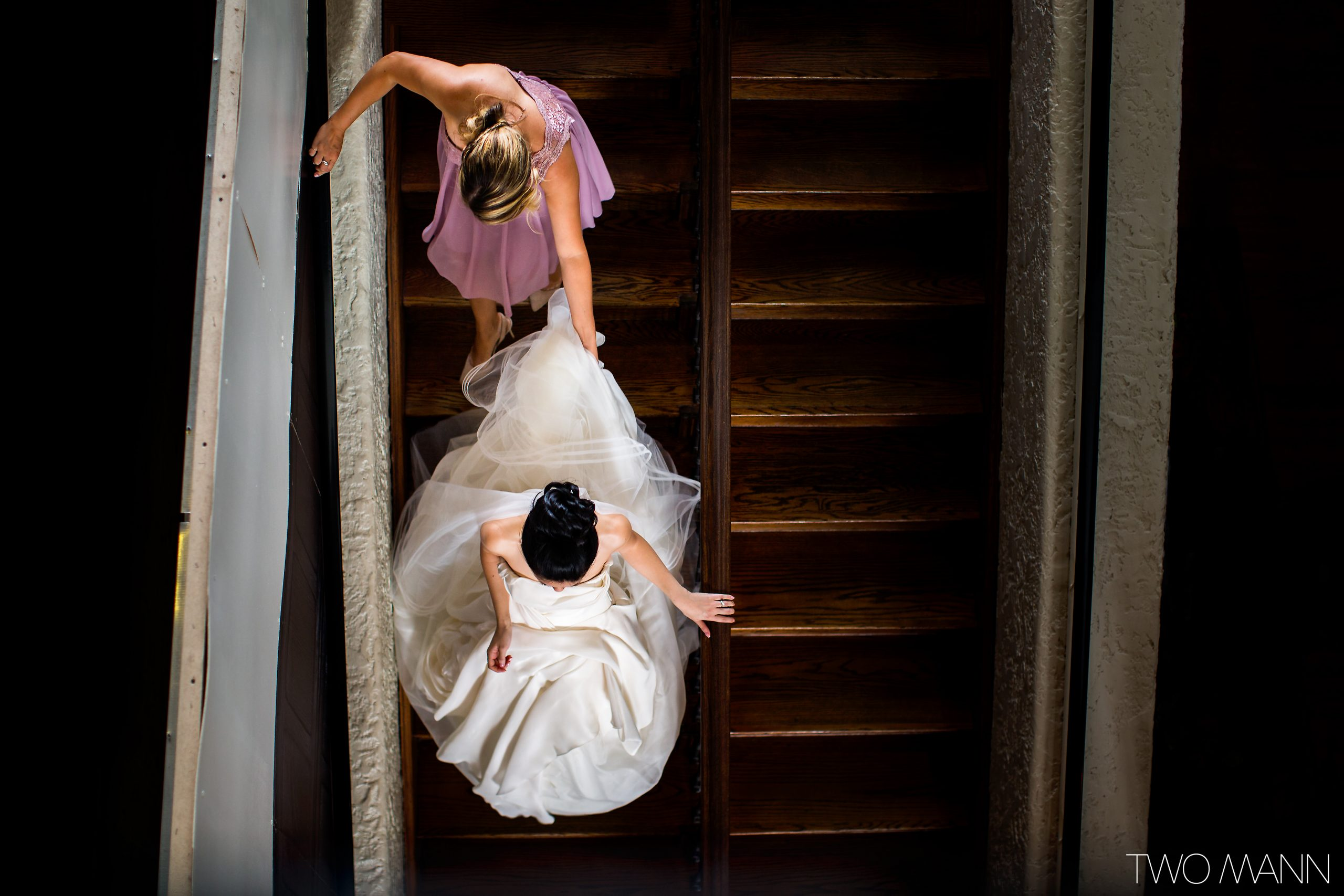 bride and bridesmaid descending stairs to ceremony