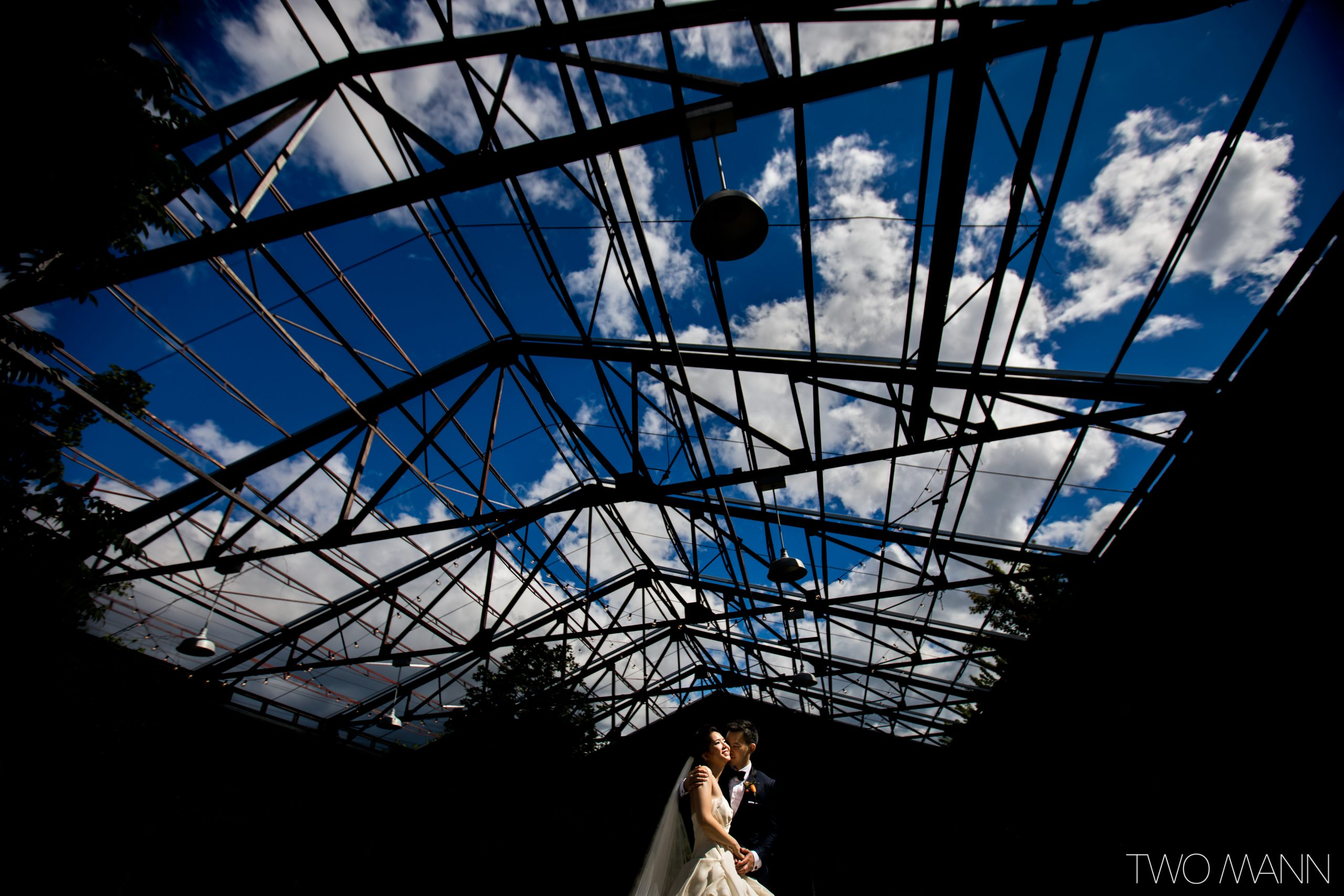 bride and groom wedding portrait beneath open architectural roof and blue sky