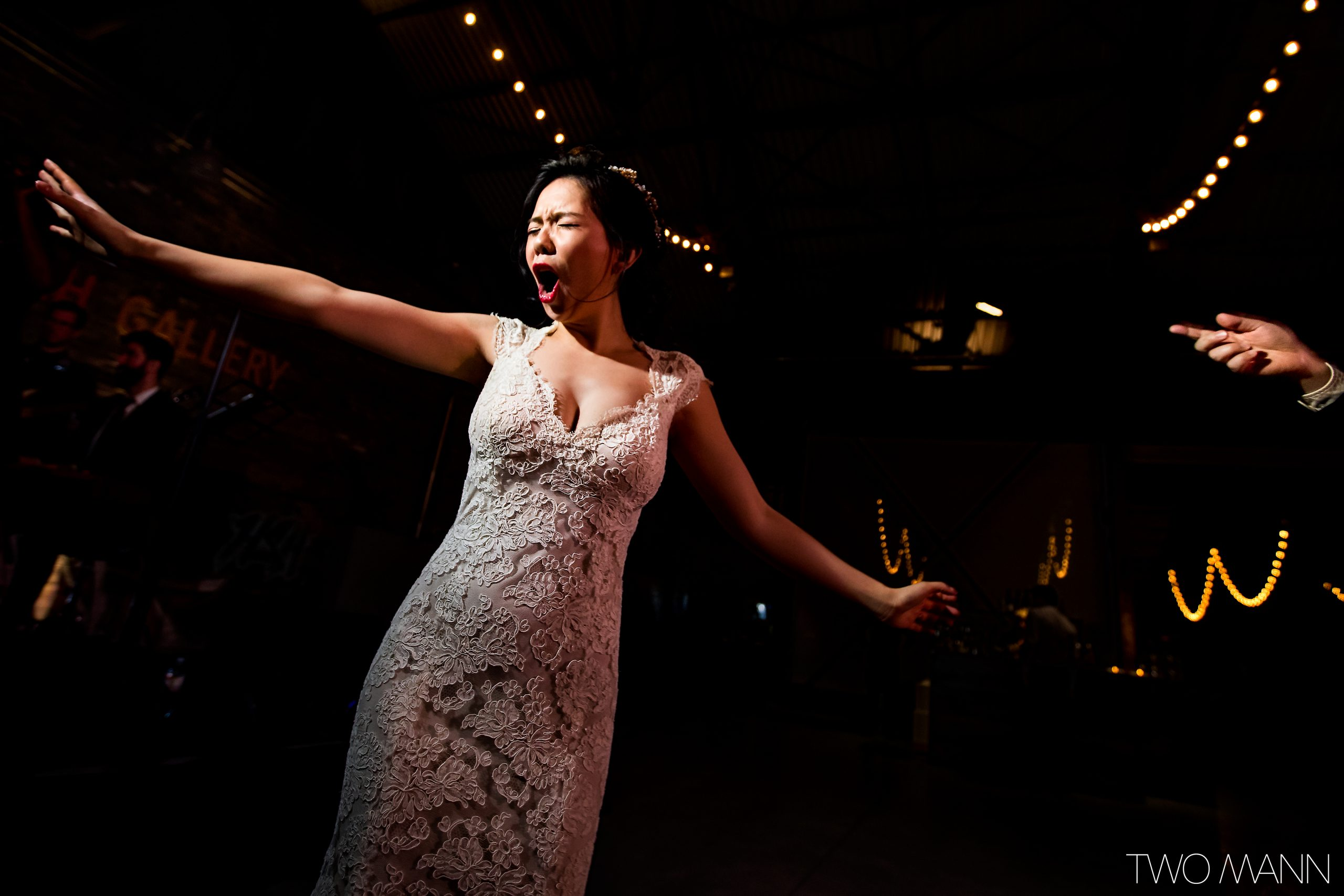 Bride dancing with arms outstretched at wedding reception party