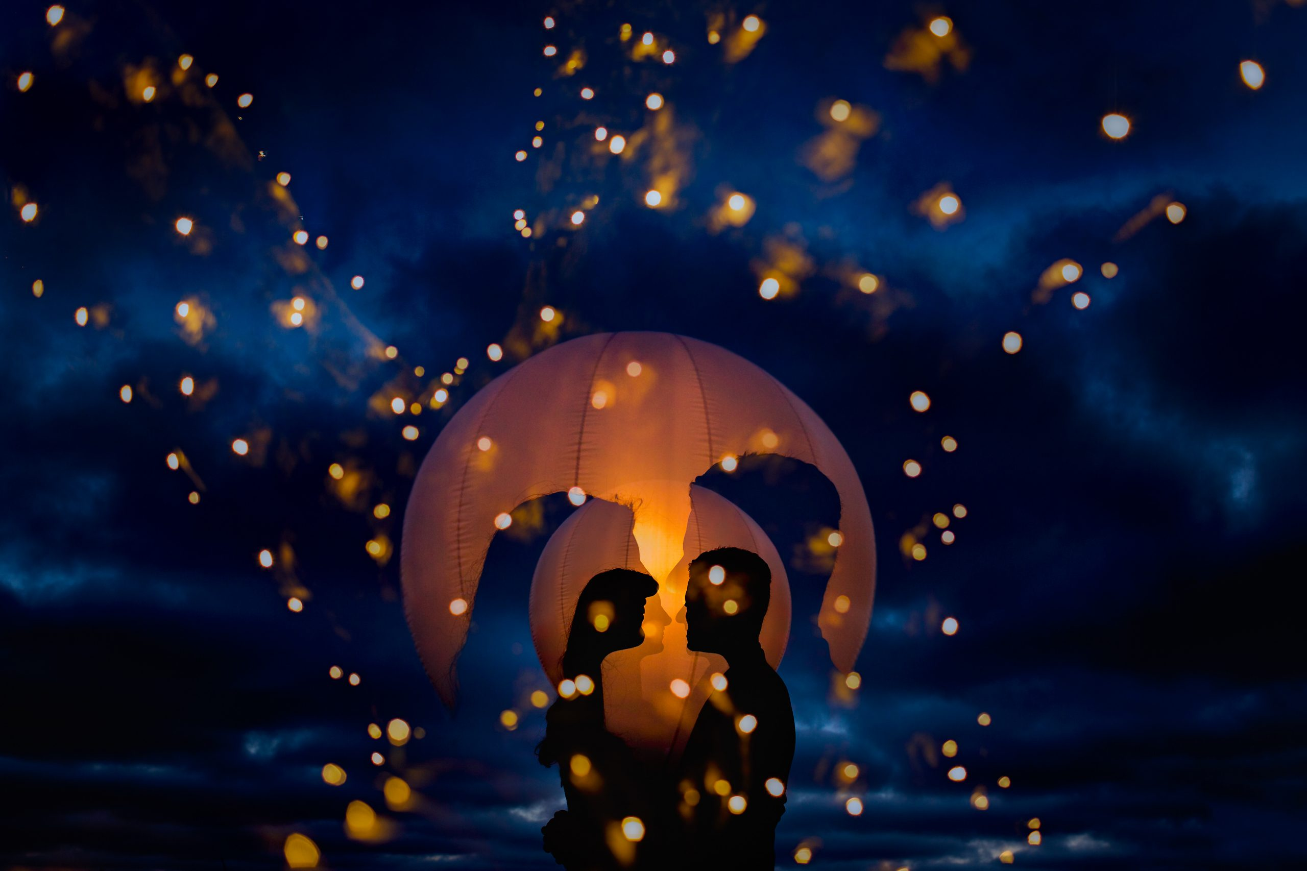 Silhouette of couple embracing with the backdrop of lights and a clouds