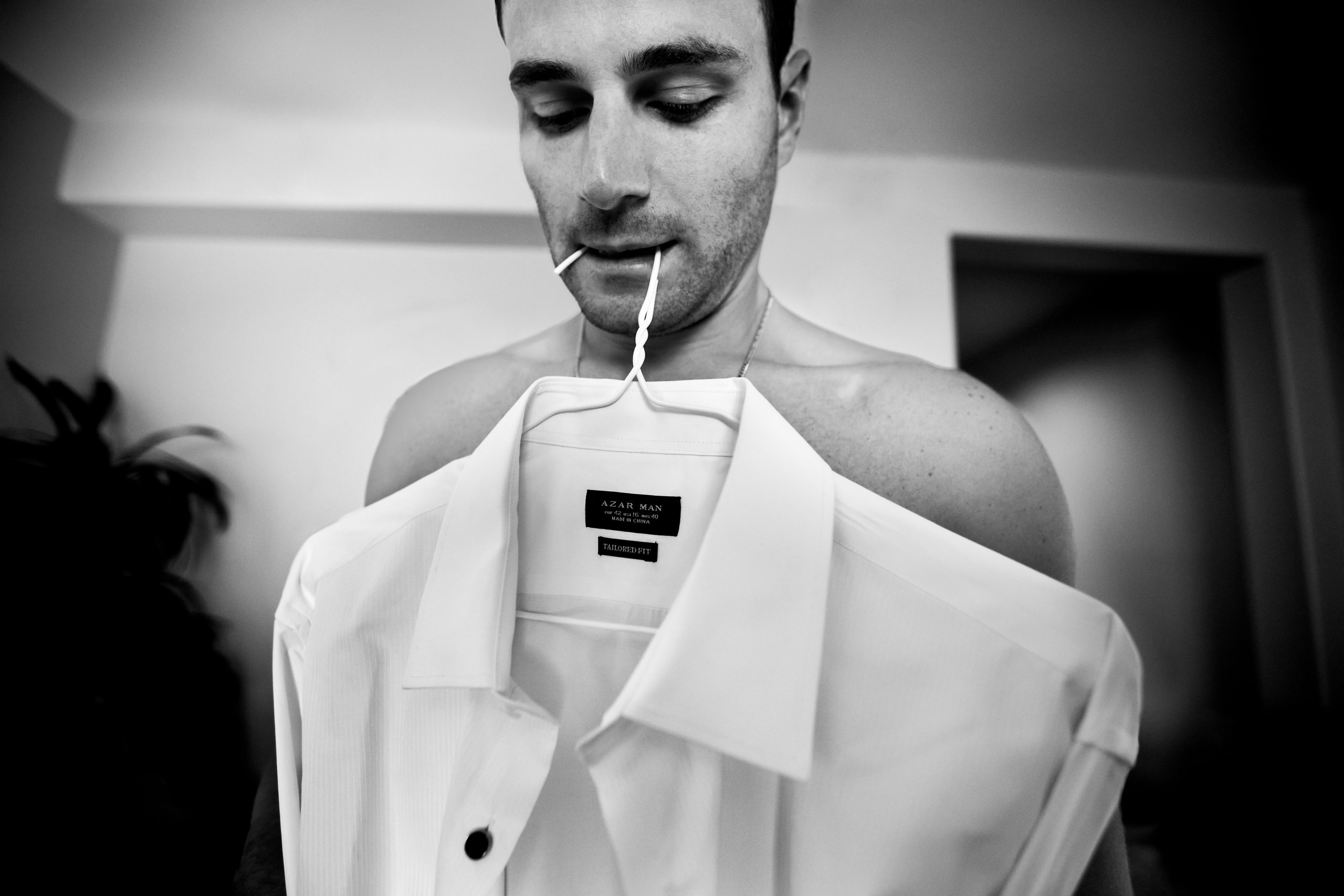 Man holds clothe hanger with a dress shirt in his mouth