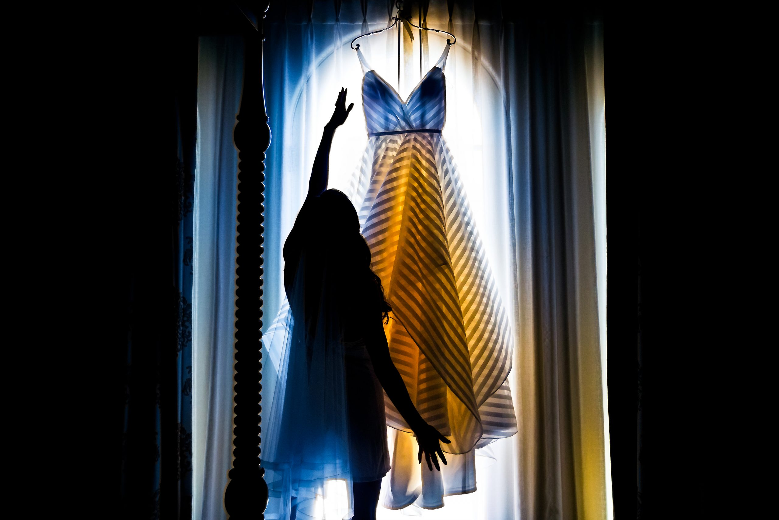 Woman inspects wedding dress hanging in front of a bright window